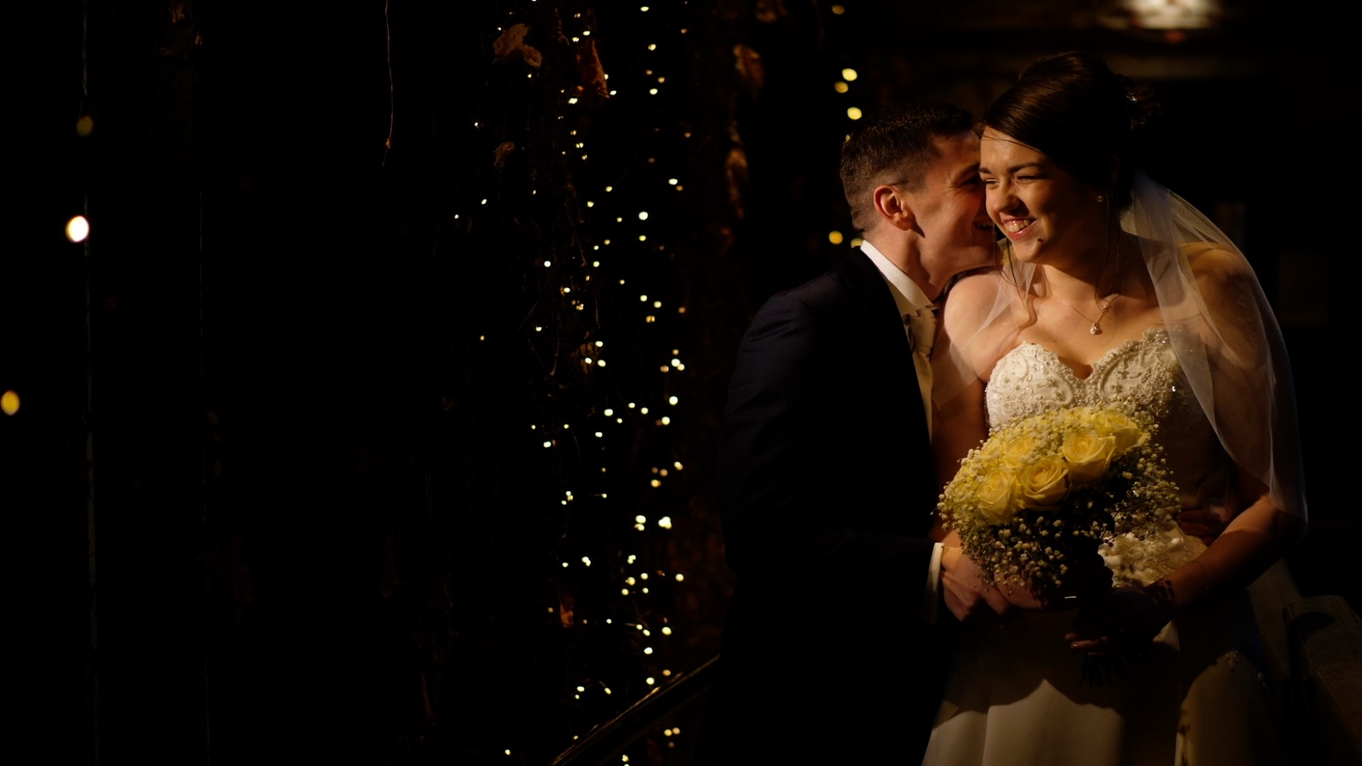 Mark whispers in Fay's ear, causing Fay to burst out in laughter. The couple share a moment in the corridor of Stirk House, which is lit by fairy lights that cascade down the walls.