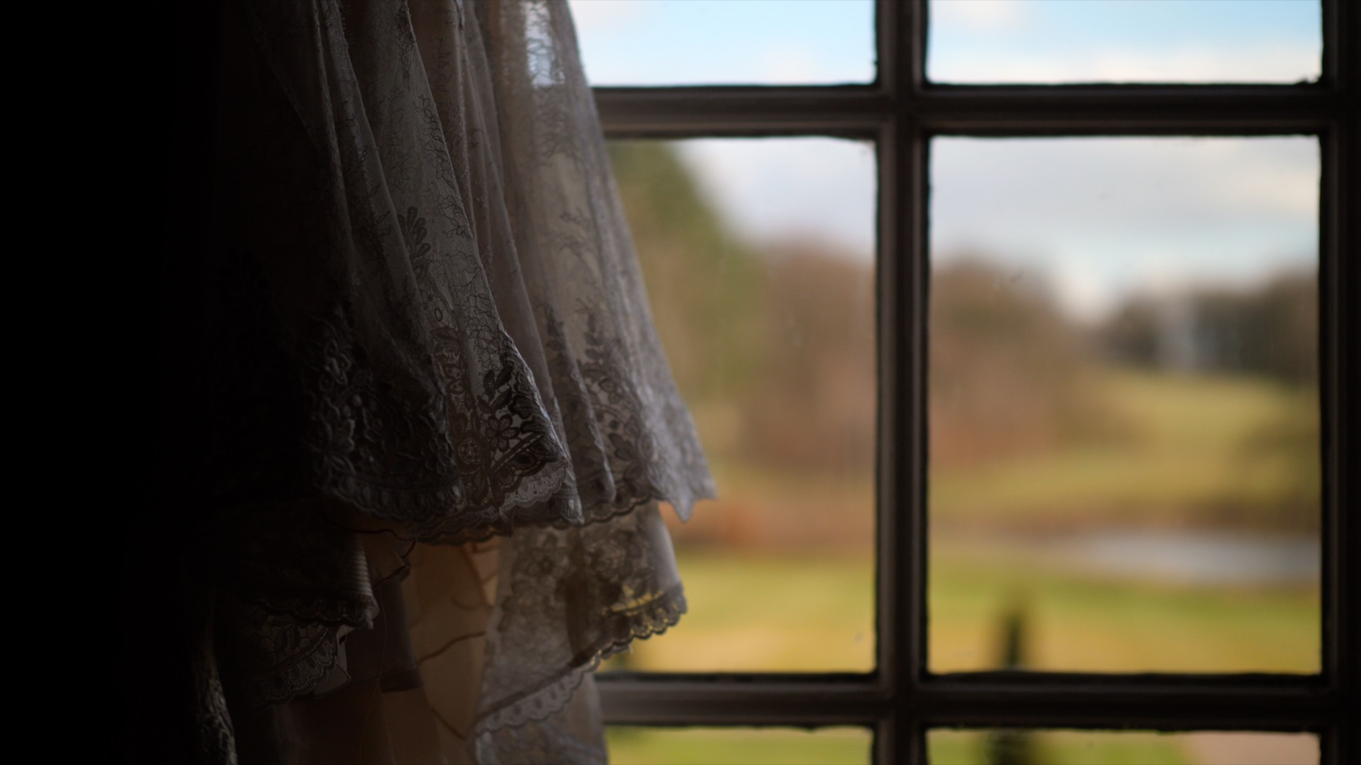 North West Wedding Videographer captures Jen's Wedding Dress hangs in the window at Knowsley Hall.