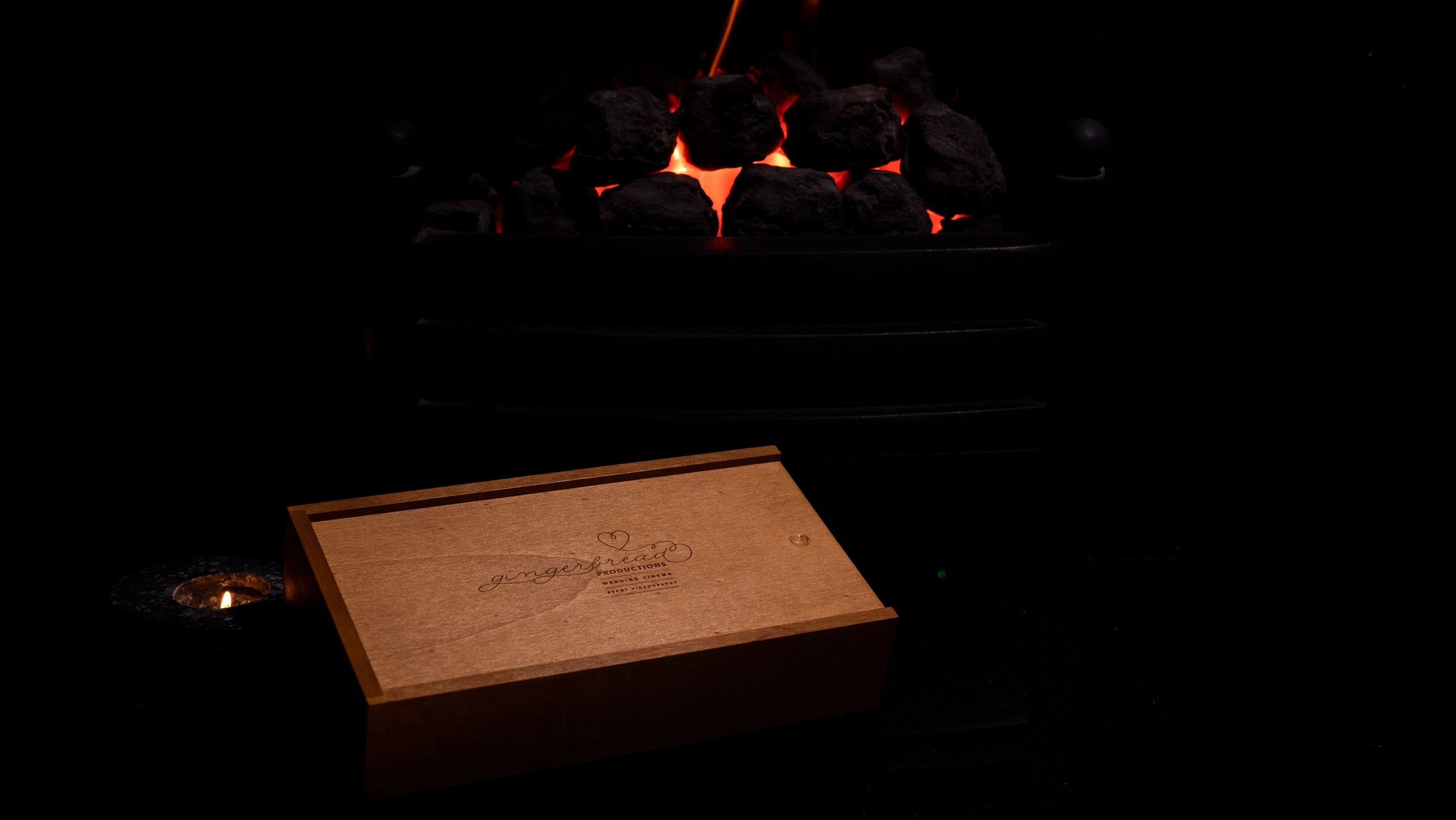 All collections come with a Gingerbread Productions USB presentation box – the perfect way to remember your wedding day! Picture shows rectangular USB box sitting in front of a fire.