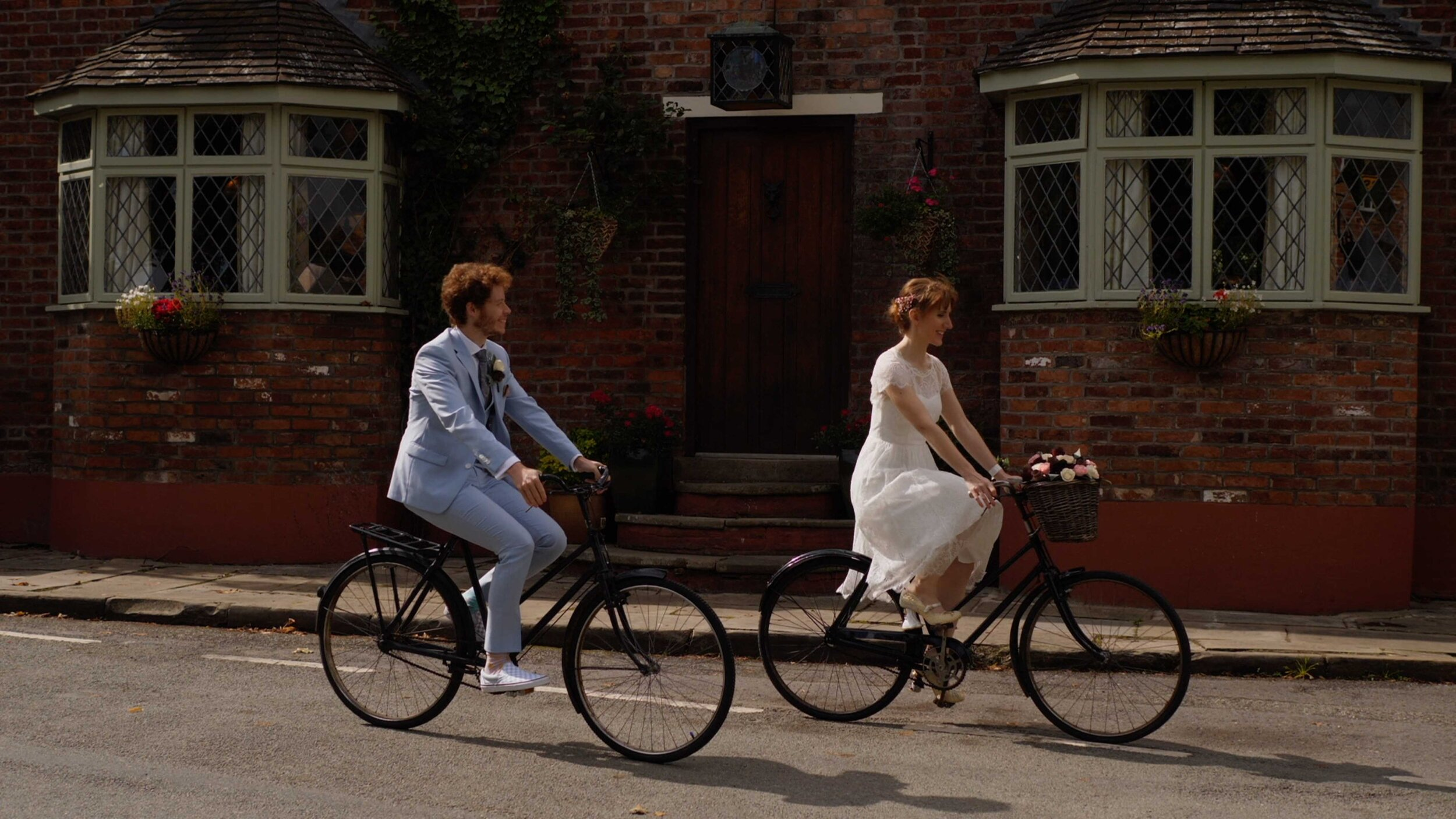 Lucy and Sam, the bride and groom, zooming along on their push bikes. Lucy is wearing a white dress, and her bike has a basket on the front, whilst Sam is wearing a sky blue suit and a smile on his face as he looks at his bride cycling alongside him.