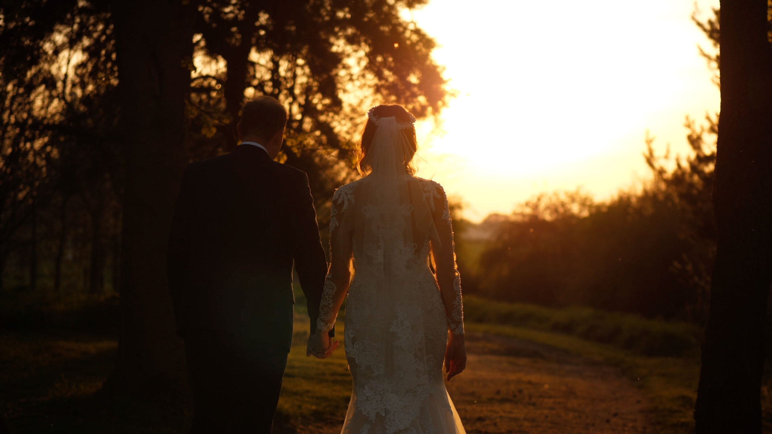 Rob and Lauren share a walk at sunset amidst a golden horizon. Walking hand in hand towards a field.