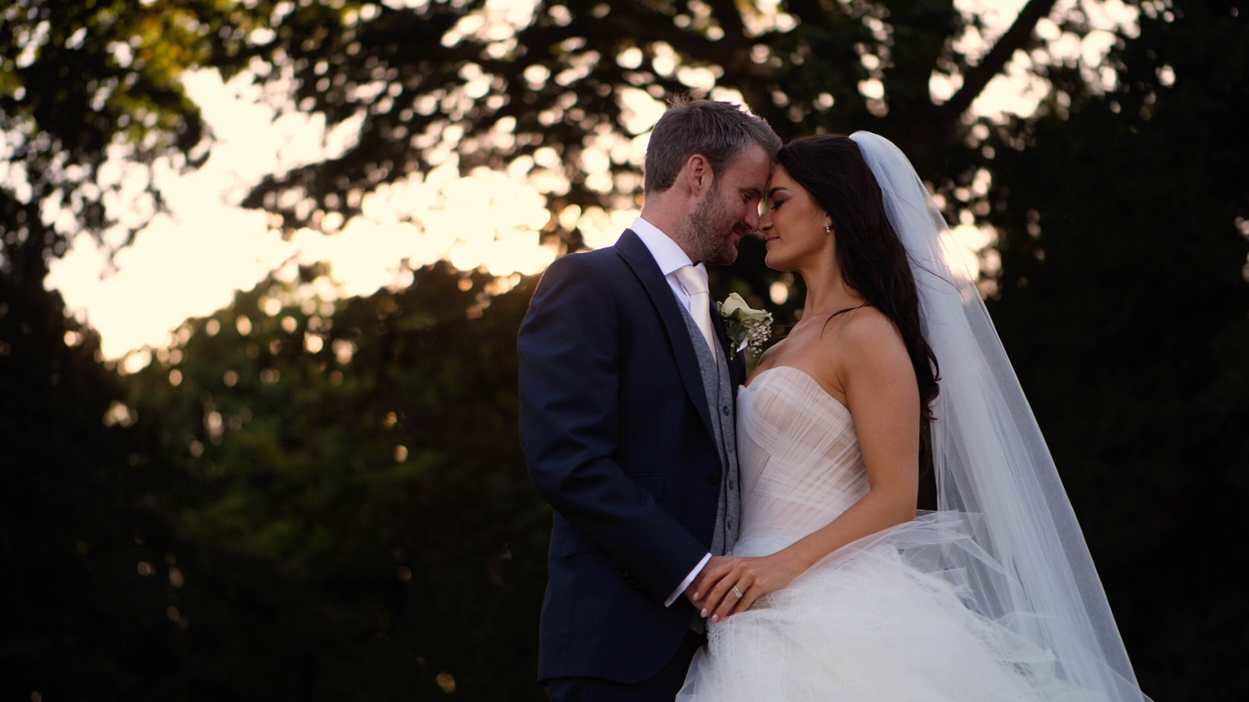 Matt + Helen share a moment in front of the sunset whilst shaded by a forest of trees at Rookery Hall.