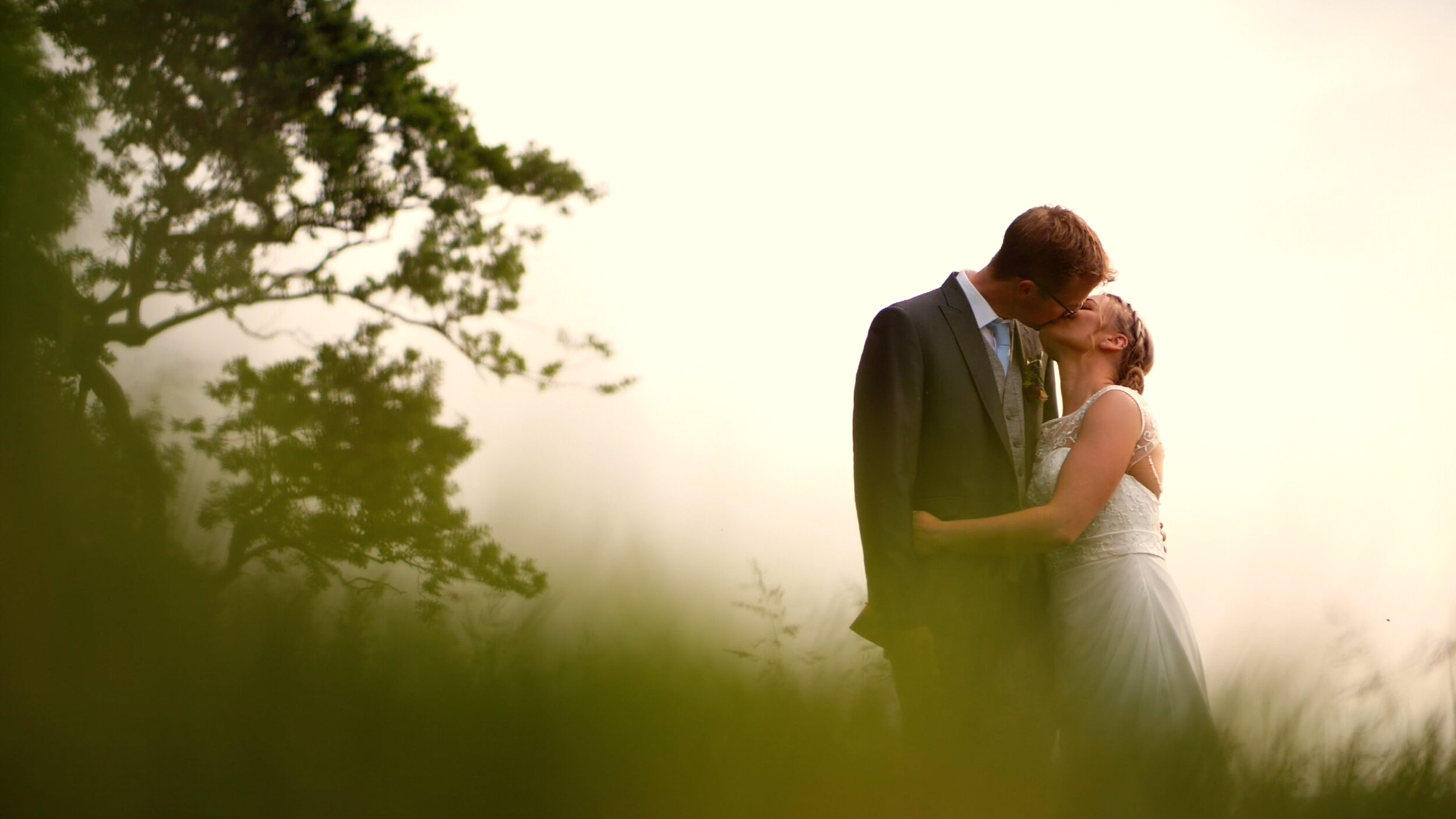 David and Lisa share a kiss amidst an overgrown field. The sun setting behind them, and the trees waving in the wind.