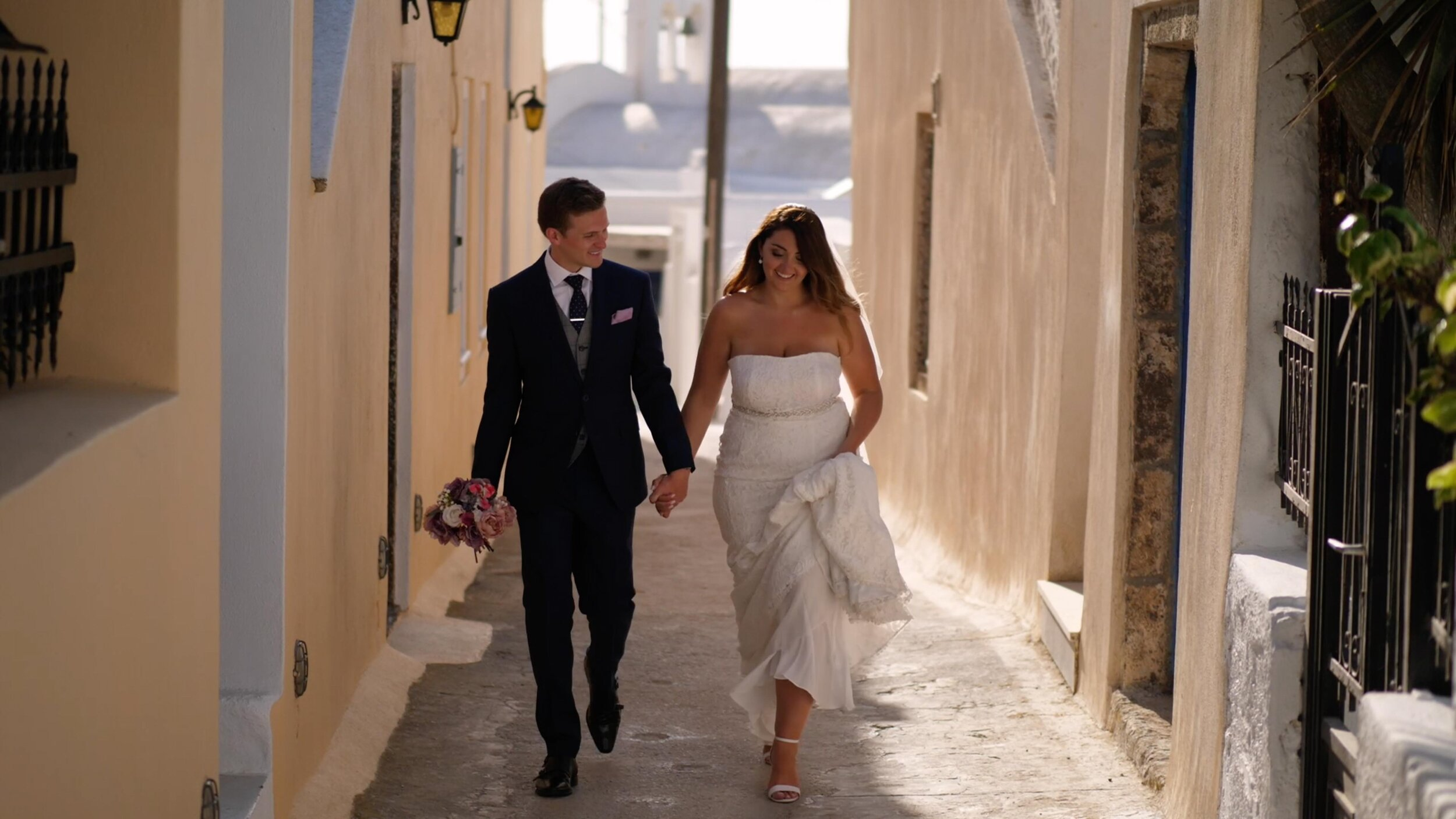 Gareth and Sara share a walk in the shade, as the sun beats down upon the backdrop. Walking through the streets of Pyrgos, Santorini, the couple walk hand in hand, as Gareth carries Sara's bouquet.