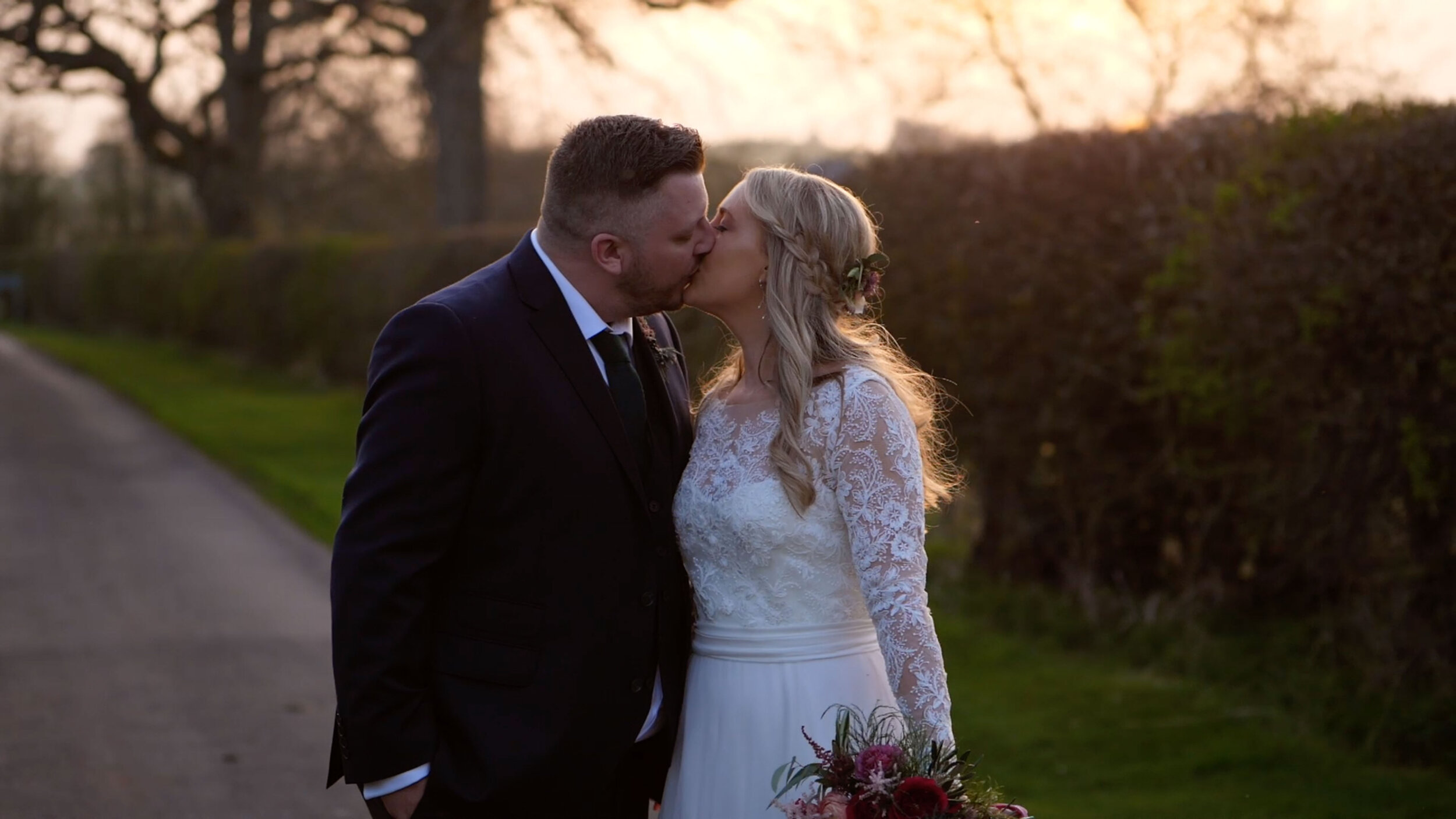 Susie and Tom share a kiss on a road beside their wedding venue, Eden Barn, Cumbria. The sunset glistens in the bride's hair, as the couple look inseparable.