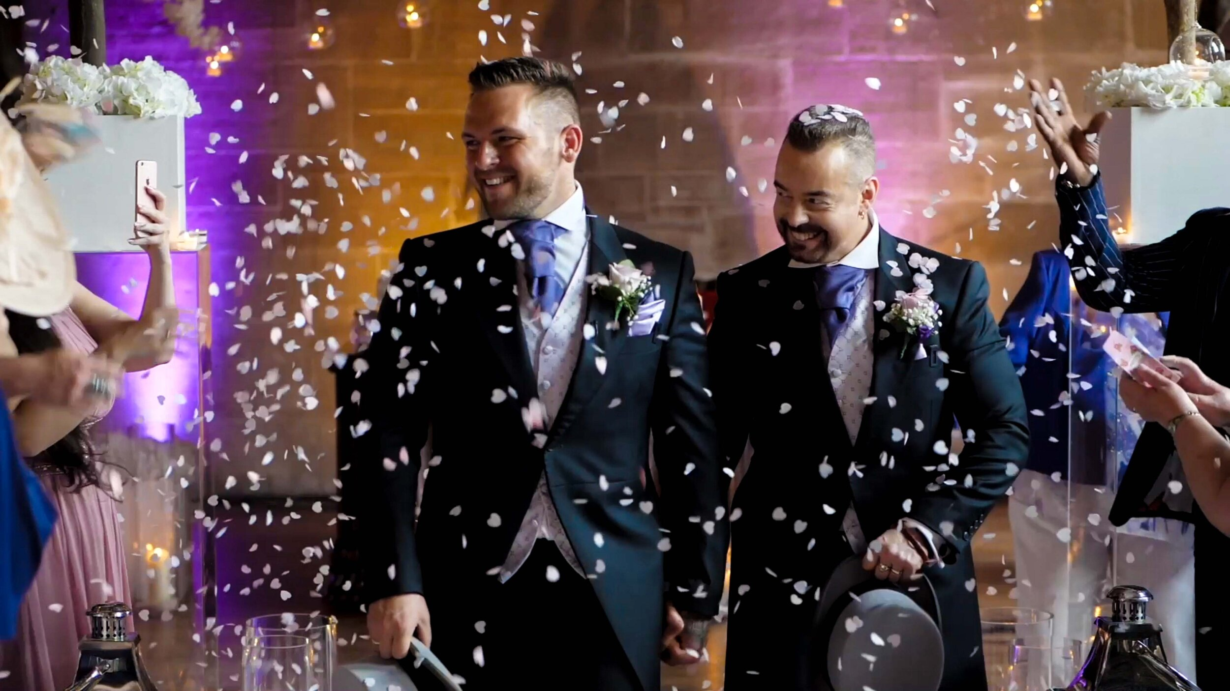 Jason and John, the bride and groom, share a walk down the aisle at Peckforton Castle. Captured by North West Wedding Videographer, Craig McKenna.