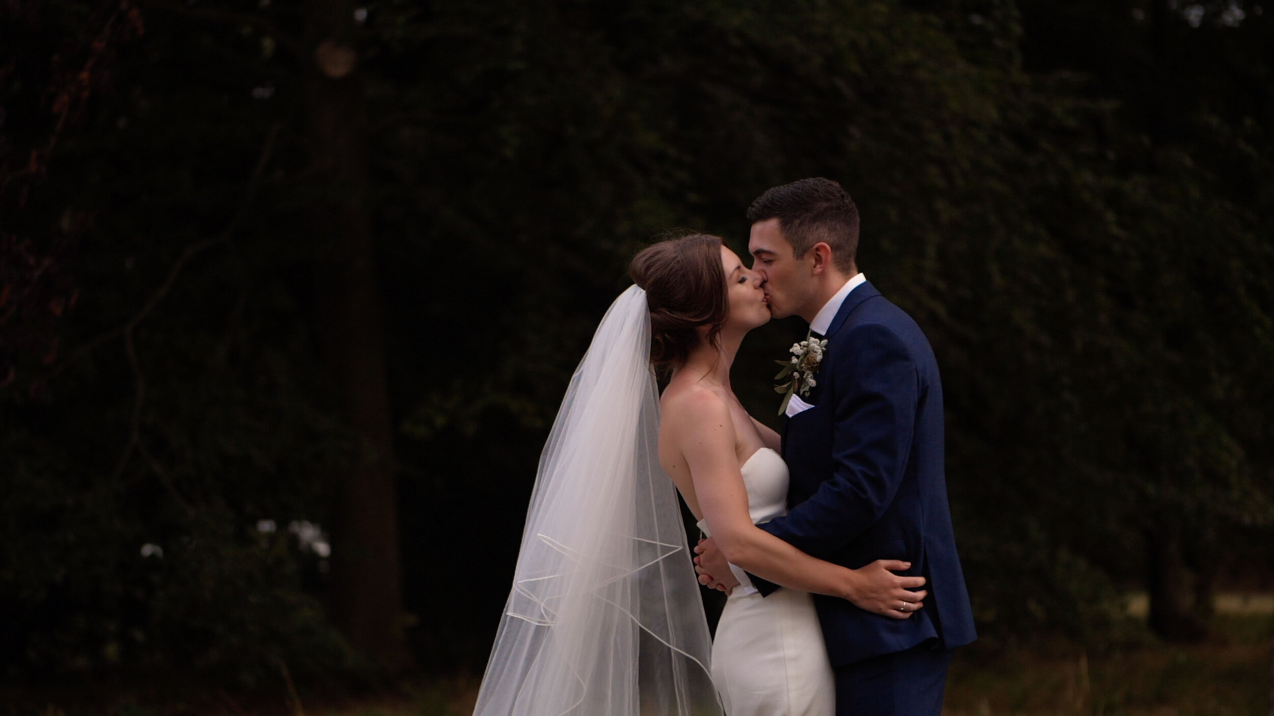 Josh and Hannah share a kiss in front of a beautiful woodland in the North West of England.