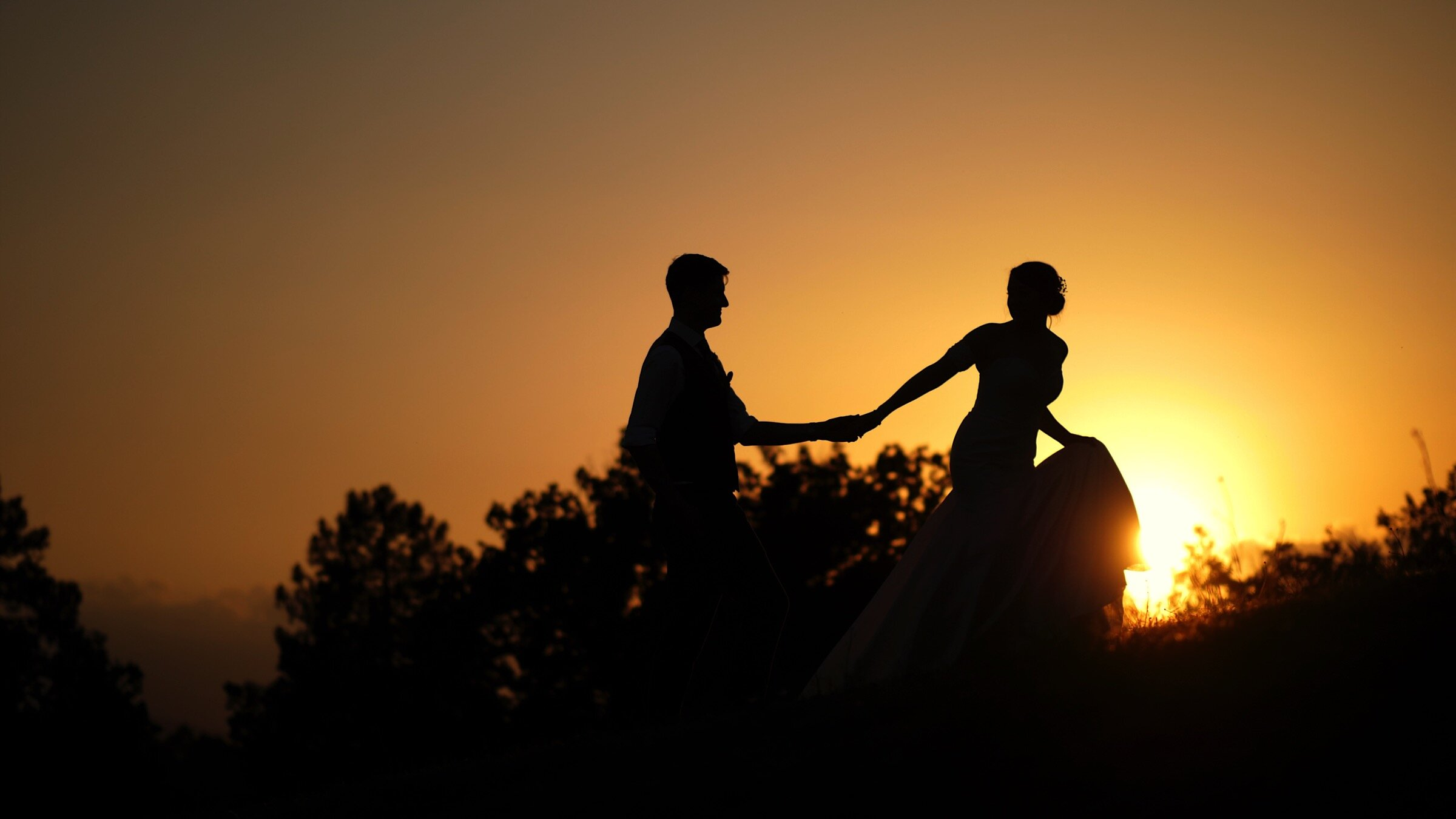 Beth and Steve share a walk, hand-in-hand, up a hill, silhouetted against a stunning Tuscan sunset.