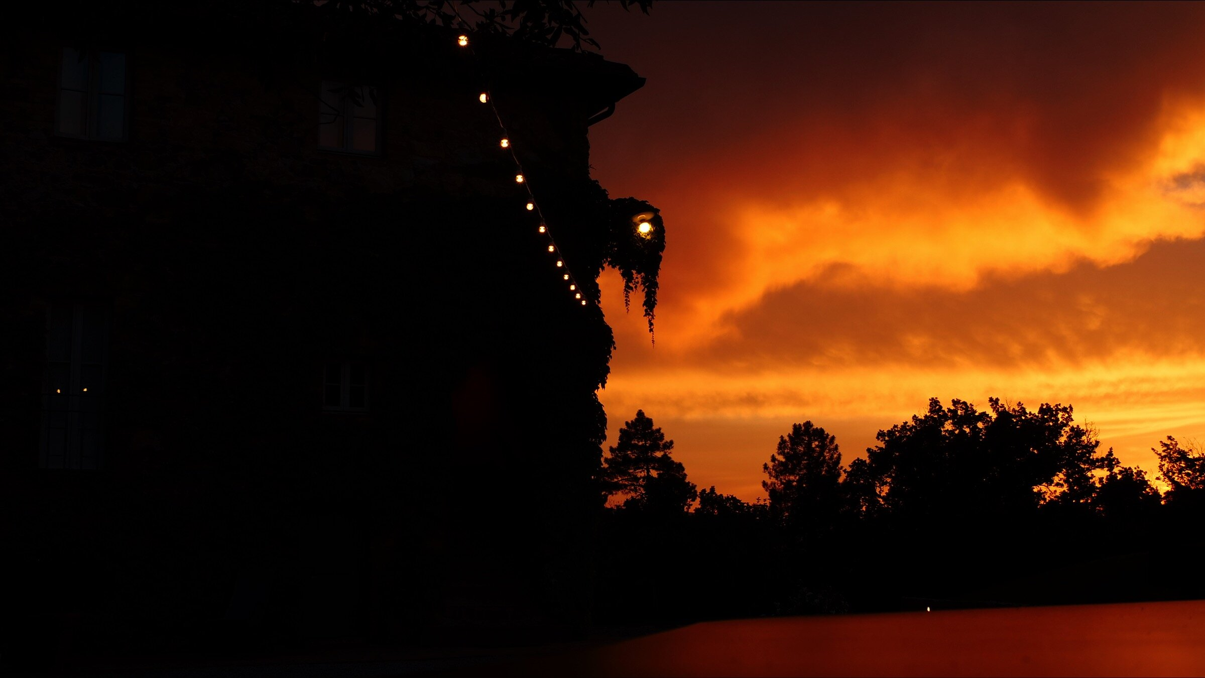 A rich, golden sunset falls behind Villa Podernovo, which is silhouetted against the sky. .