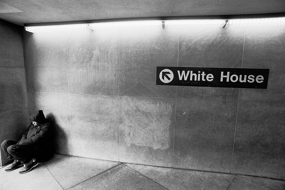 A homeless man protects himself from the wind at the entrance of a Metro station near the White House.  November 2005.  © Kike Arnal