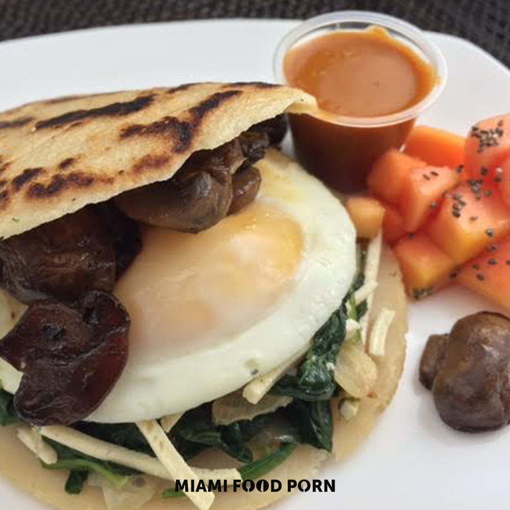 Arepa breakfast sandwich with sunny side up egg.
