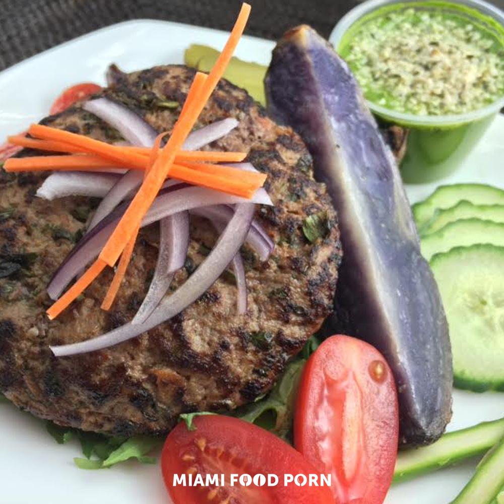 Grass-fed burger with sun-dried tomato hemp pesto, steak fries & kale salad.