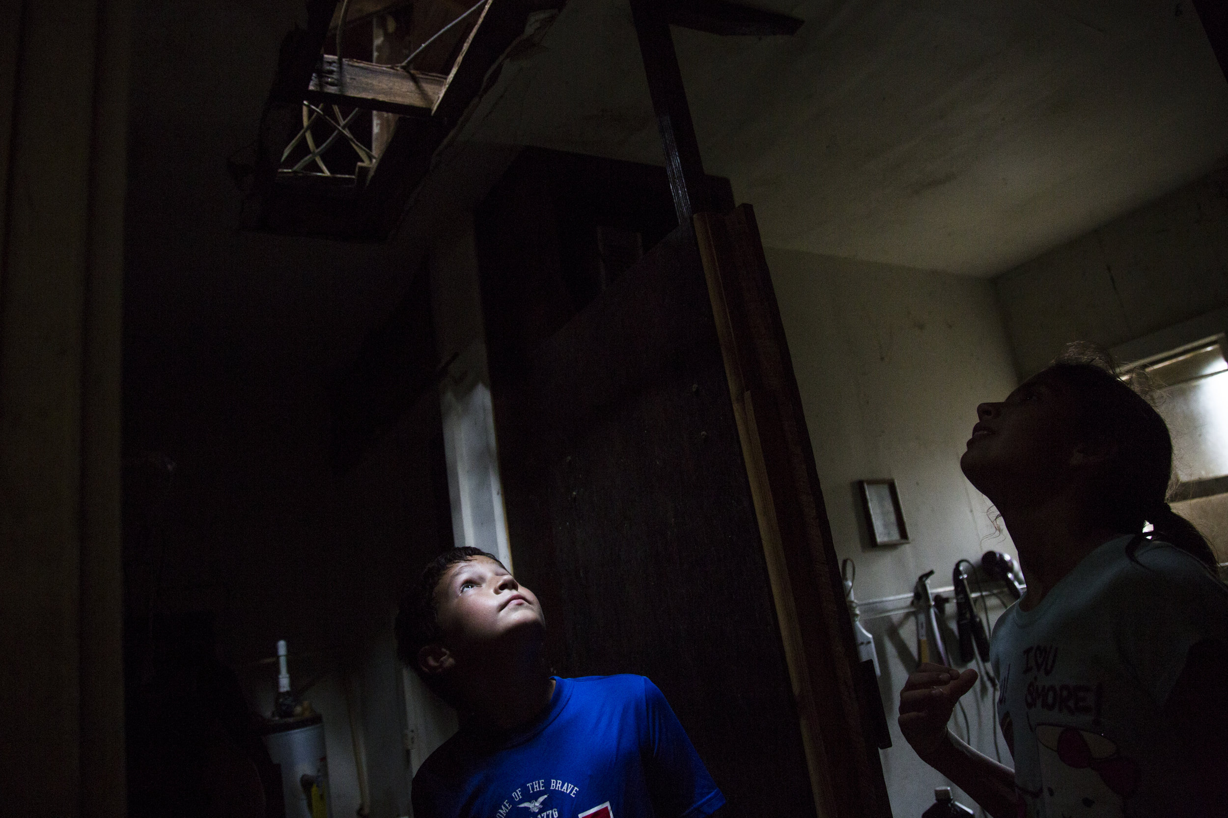 Kyler Carpenter, 10, left, and Laela Carpenter, 11, look up through a hole that was torn in their roof by Hurricane Harvey. The cousins surveyed the damage Sunday to Laela's family home in Bayside, Texas.