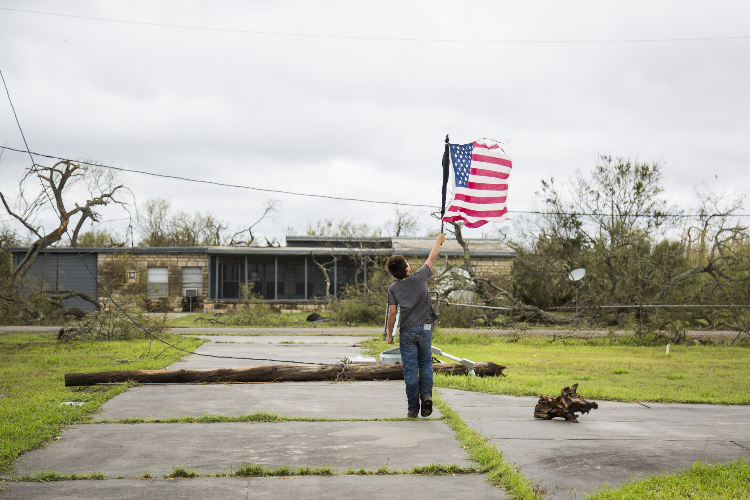 Layton Carpenter, 12, walks down an empty driveway in Bayside holding a broken American flag that he found in the water after the hurricane hit Bayside.