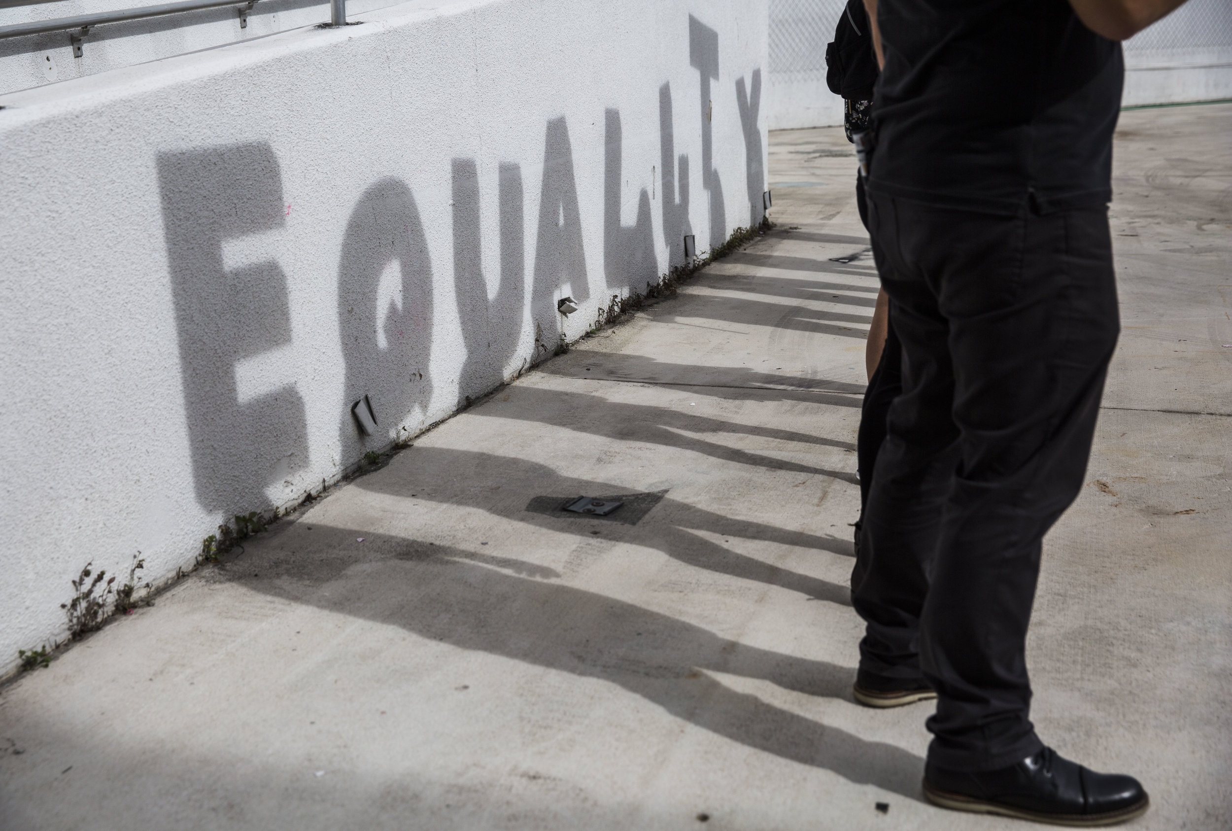 "A shadow spelling out ""equality"" is cast against a wall as a part of an art piece set up at the Women's March Florida at Mana Wynwood in Miami on Jan. 21, 2018."