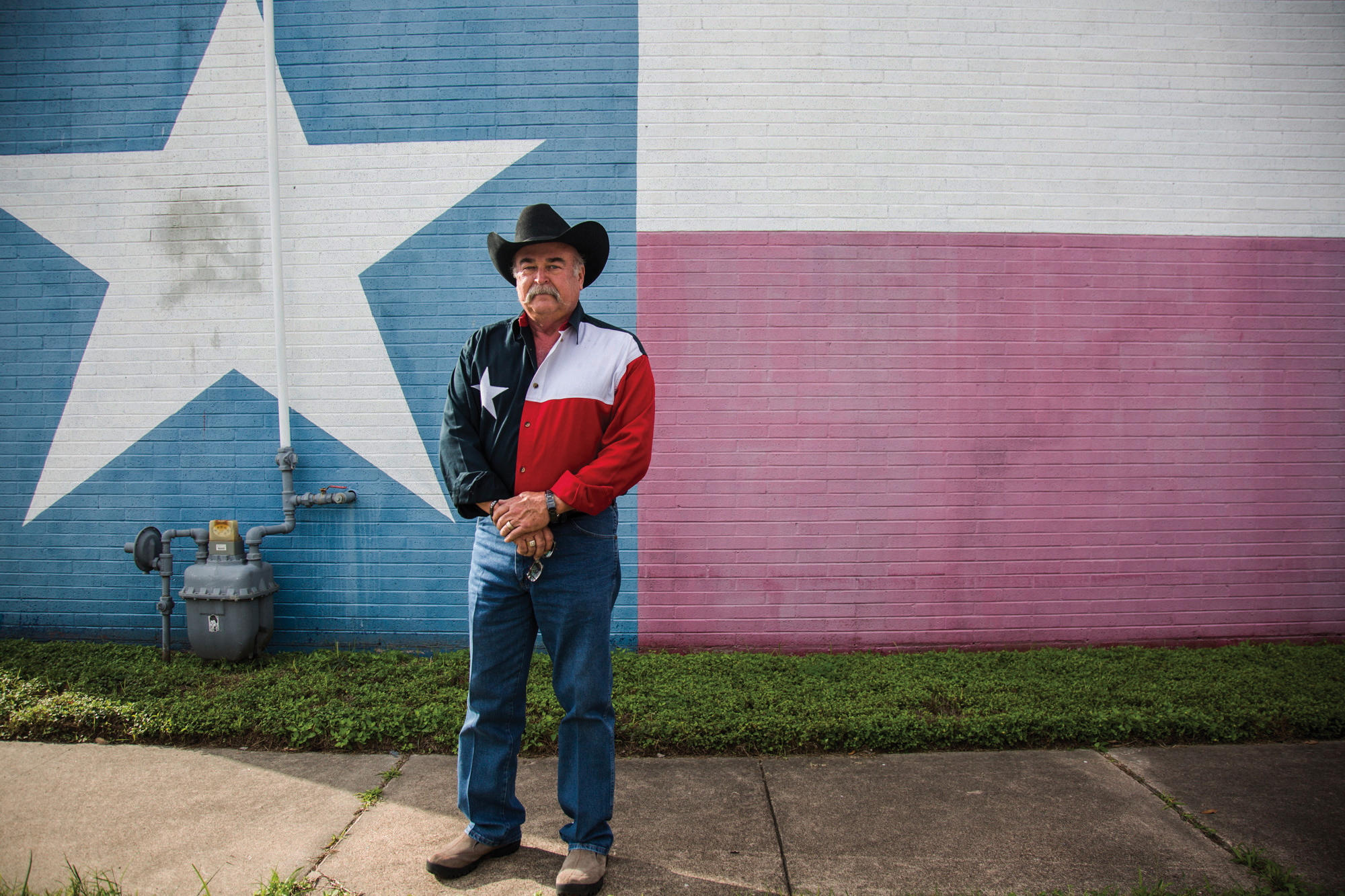 Thomas Smith, 66, stands in front of a Texas flag wall painting with a matching Texas flag shirt waiting for the start of the Veterans Day parade in Victoria, Texas on Nov. 11, 2017.