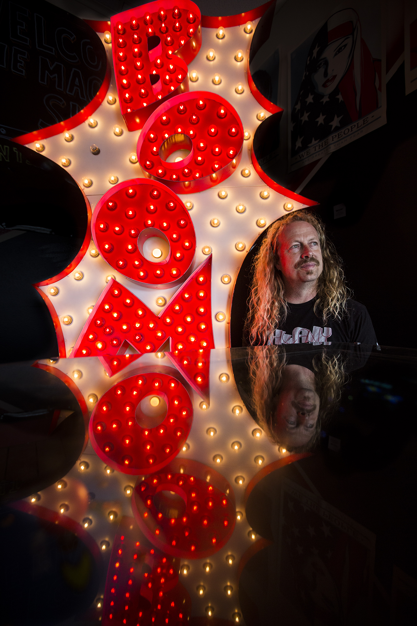 "Tim Leonard, metal worker and owner of The Machine Shop pinball arcade, with one of his lighted metal ""BOOM"" sign on display at The Machine Shop on Thursday, July 18, 2019 in Langley, Wash."