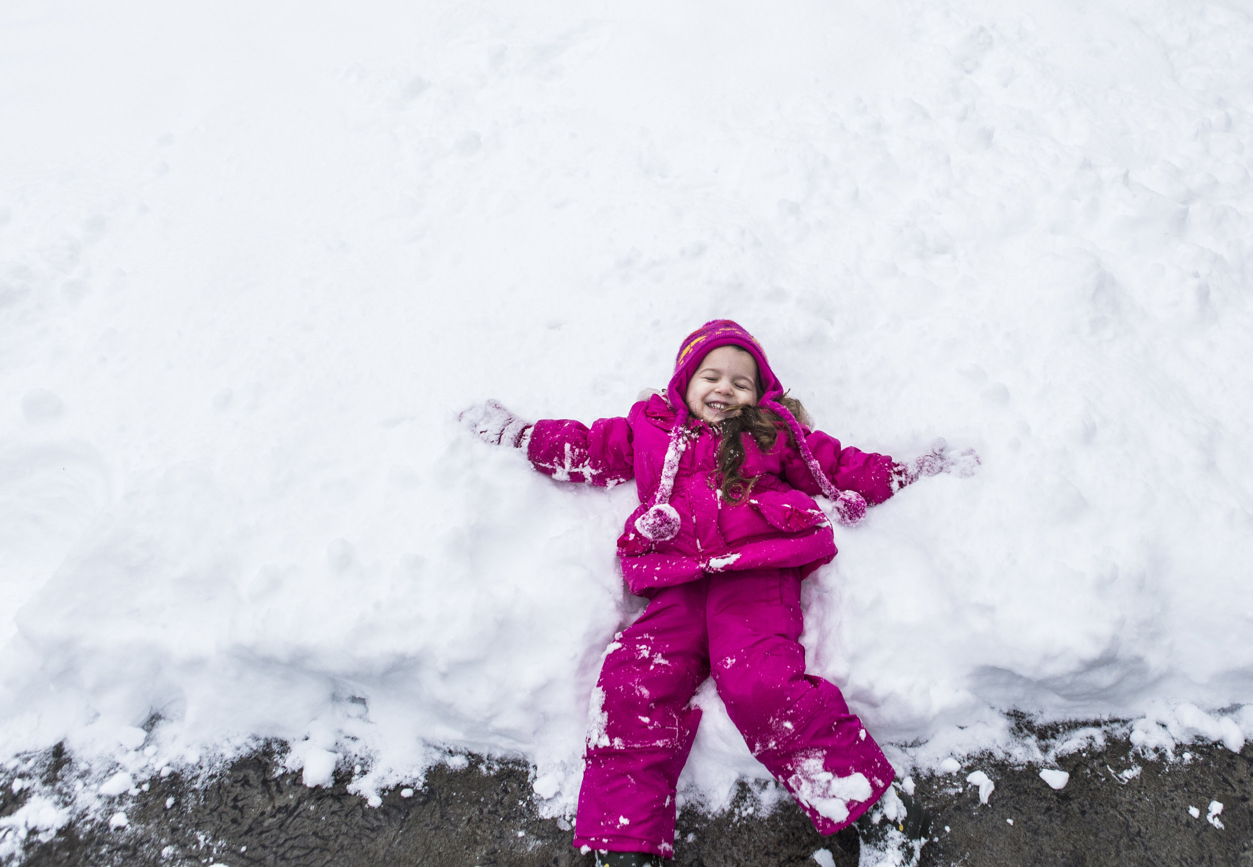 Kaylee Williams, 3, smiles as she makes her first snow angel of the day in the front yard of her family's home on Saturday, Feb. 9, 2019 in Everett, Wa. The Puget Sound area was hit by the a massive snowstorm for the second time in two weeks resulting in upwards of a foot of snow in some areas of Snohomish county.