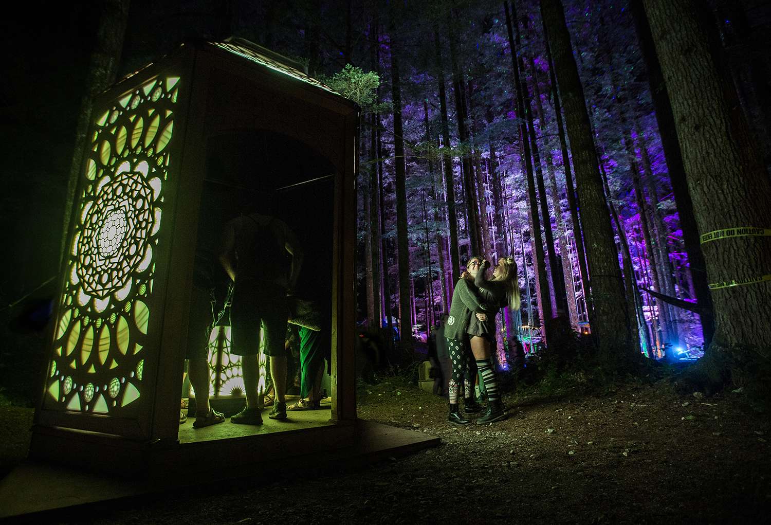 Two friends hug each other as they explore the Axis Mundi art installation at the Summer Meltdown on Thursday, Aug. 2, 2018 in Darrington, Wa.