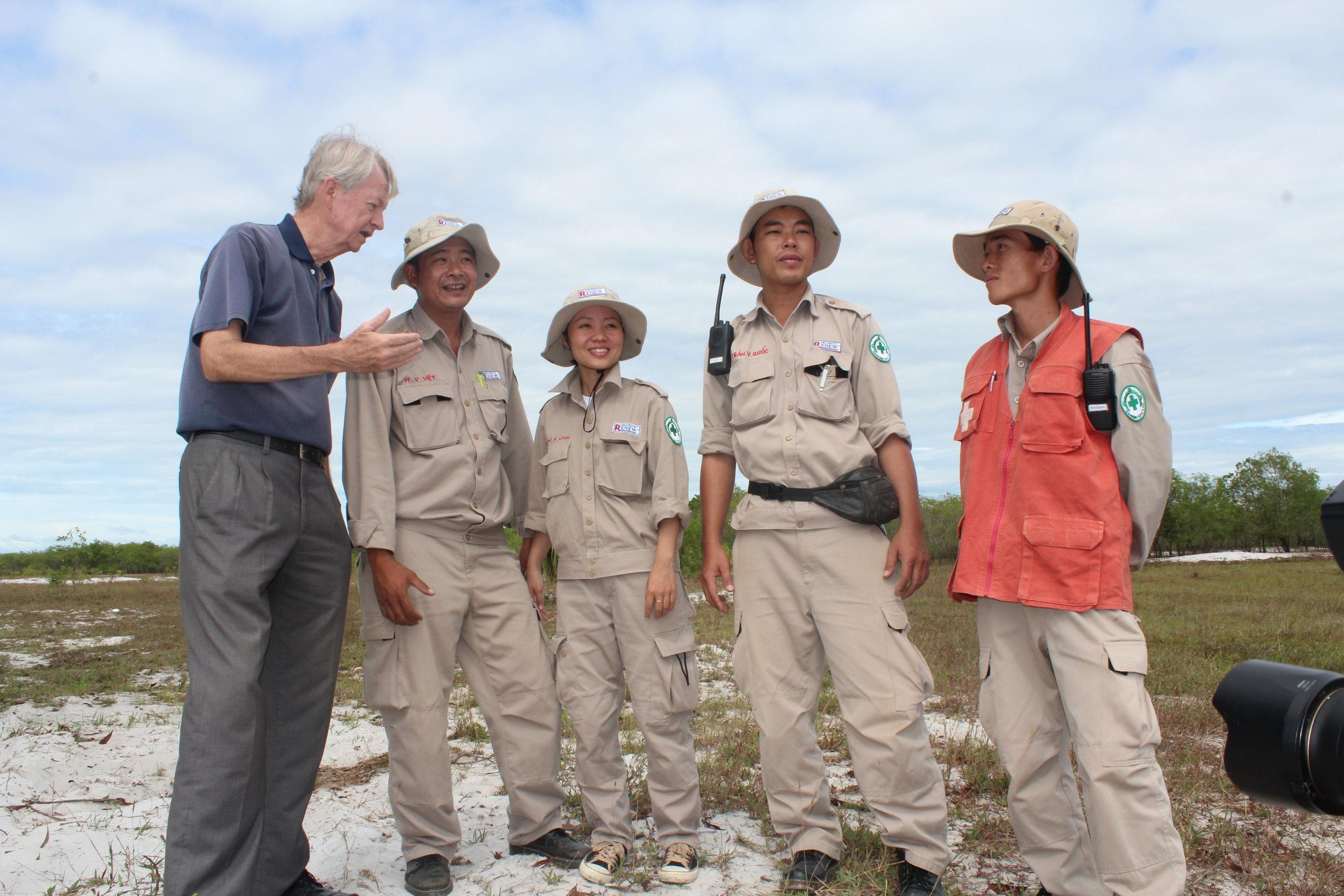 Chuck Searcy talks with Project RENEW team members after a UXO demolition. Photo courtesy Chuck Searcy.Ông Chuck trò chuyện với thành viên đội Project RENEW sau khi phá dỡ thành công bom mìn chưa nổ. (UXO)