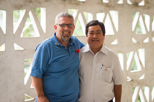 """Mike Burkett with Ho Van Hien. Mike, whose father Curtis Earl Burkett, was killed on February 19, 1971 in Quang Ngai Province, has many family photos of his parents, but only one with him in it. Mr. Hien's father was killed in 1968 when Mr. Hien was four months old. He has no memories, and no pictures, of his father. We asked if anyone told him anything about his dad, he recalled what his mother said: his father fought bravely """"until his last bullet."""""""