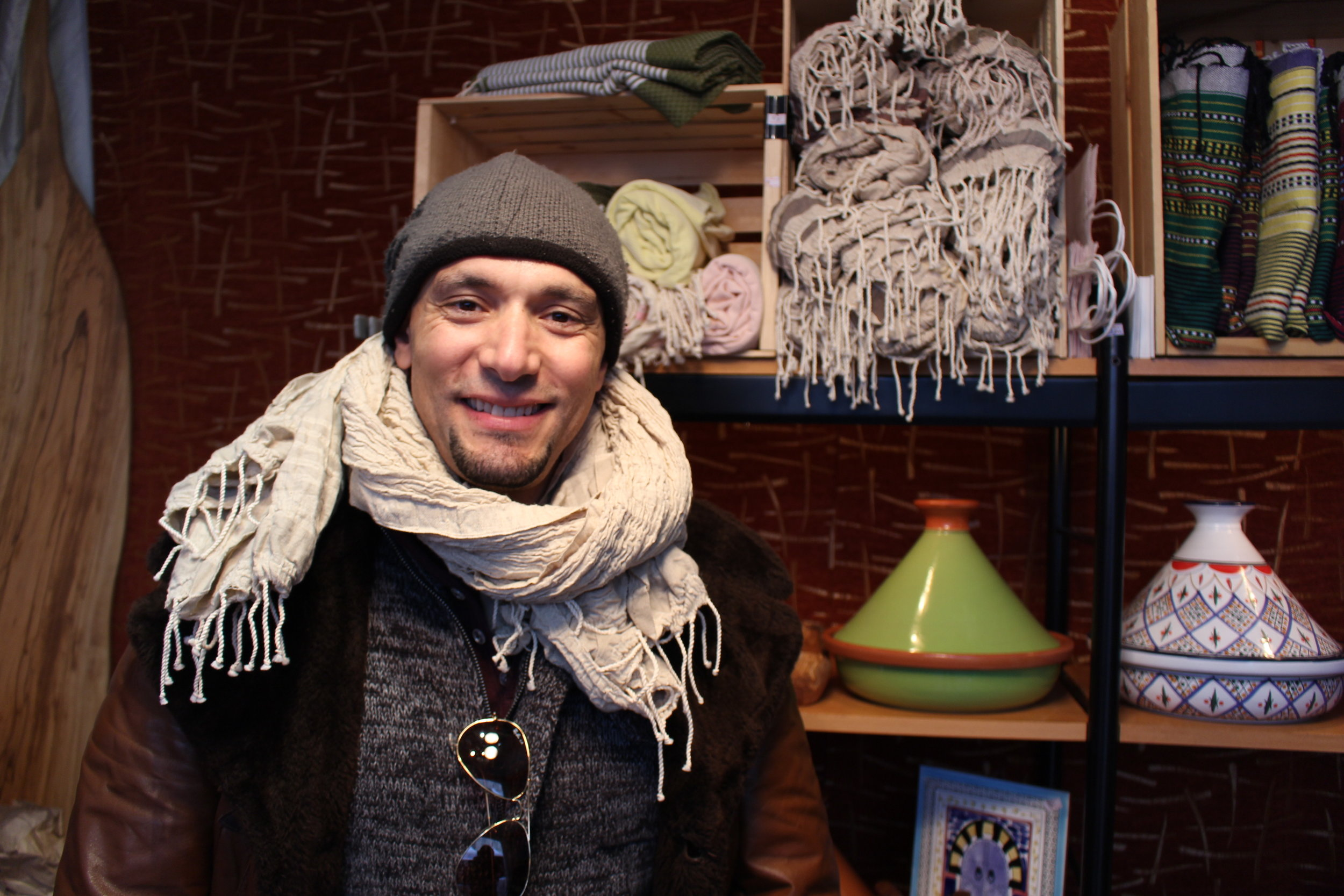 Naj Ajroud in his boutique at the Downtown Holiday Market poses proudly in front of his Tunisian scarves and cooking pots. Photo by Natalie Hutchison.