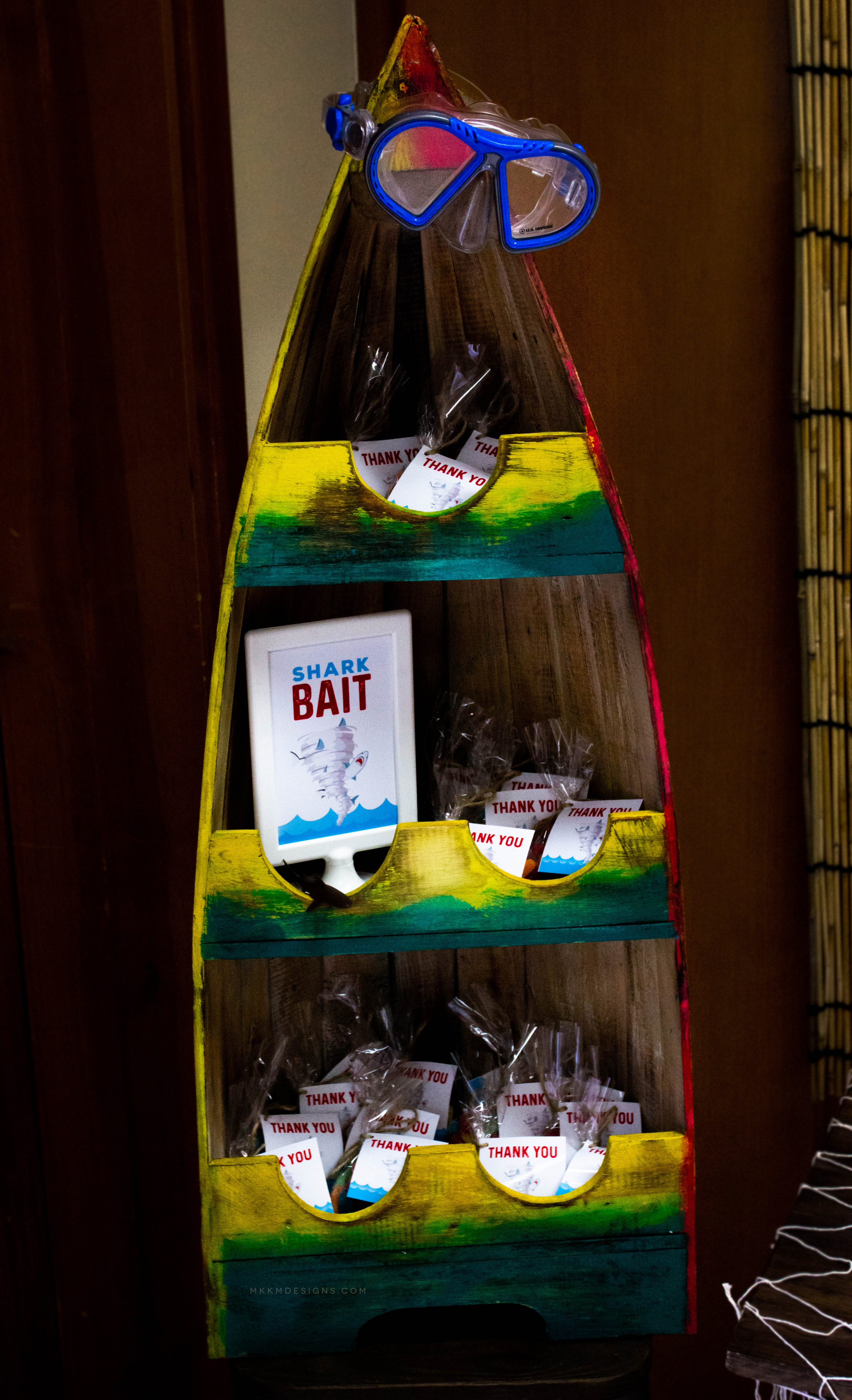 Boat shaped wine rack used as a favor holder at a Shark Birthday Party // mkkmdesigns