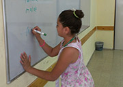 "Mariam writes her name on the board in Tourism class, taught by Ms. Kochav. The trickiest part of today's class was learning the proper enunciation of ""Annunciation."""