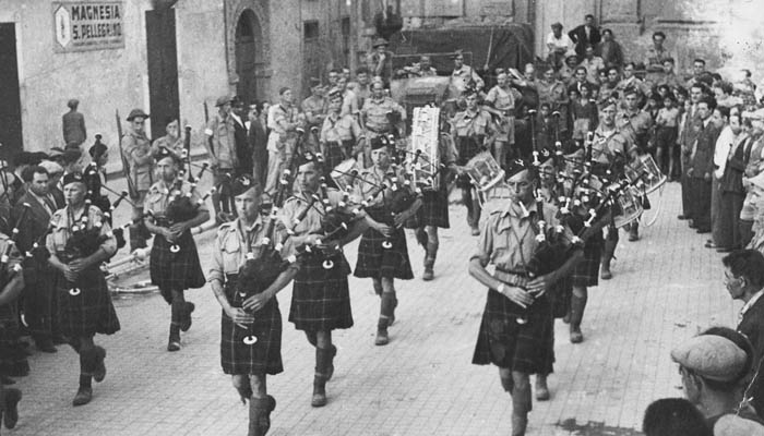 The Seaforth Pipes and Drums plays <<retreat>> in Agira's main square on the evening the town was captured. A CBC recording of the event was broadcast around the world.