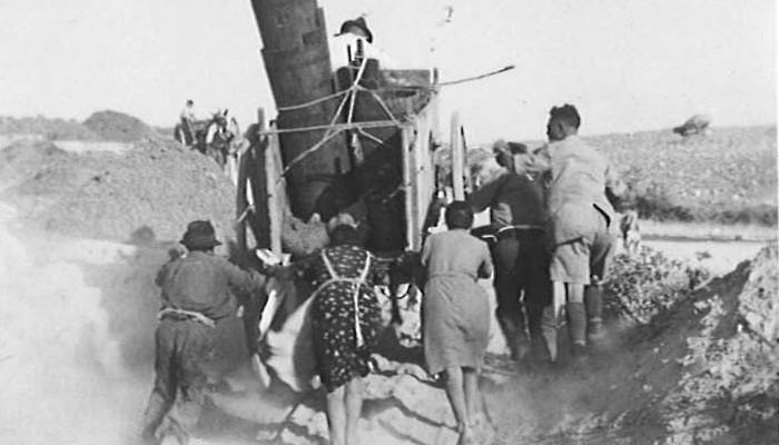 Seaforth soldiers assisting local Sicilian refugees with pushing their wagon full of household effects.