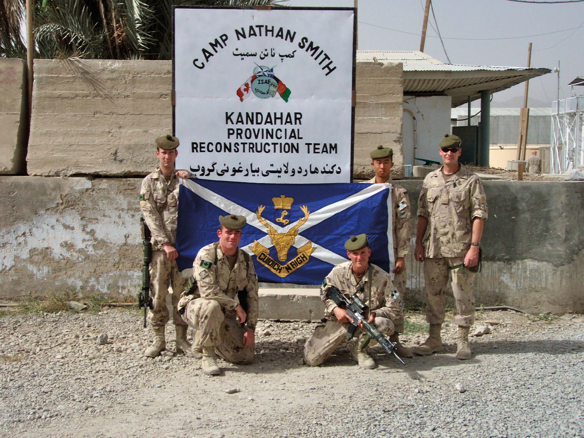 Corporal Josh Muir, Sergeants Stacey Shannon and Sean Laloge, and Corporals Jason Lacharite and Brian Lim near the front gate of Camp Nathan Smith.
