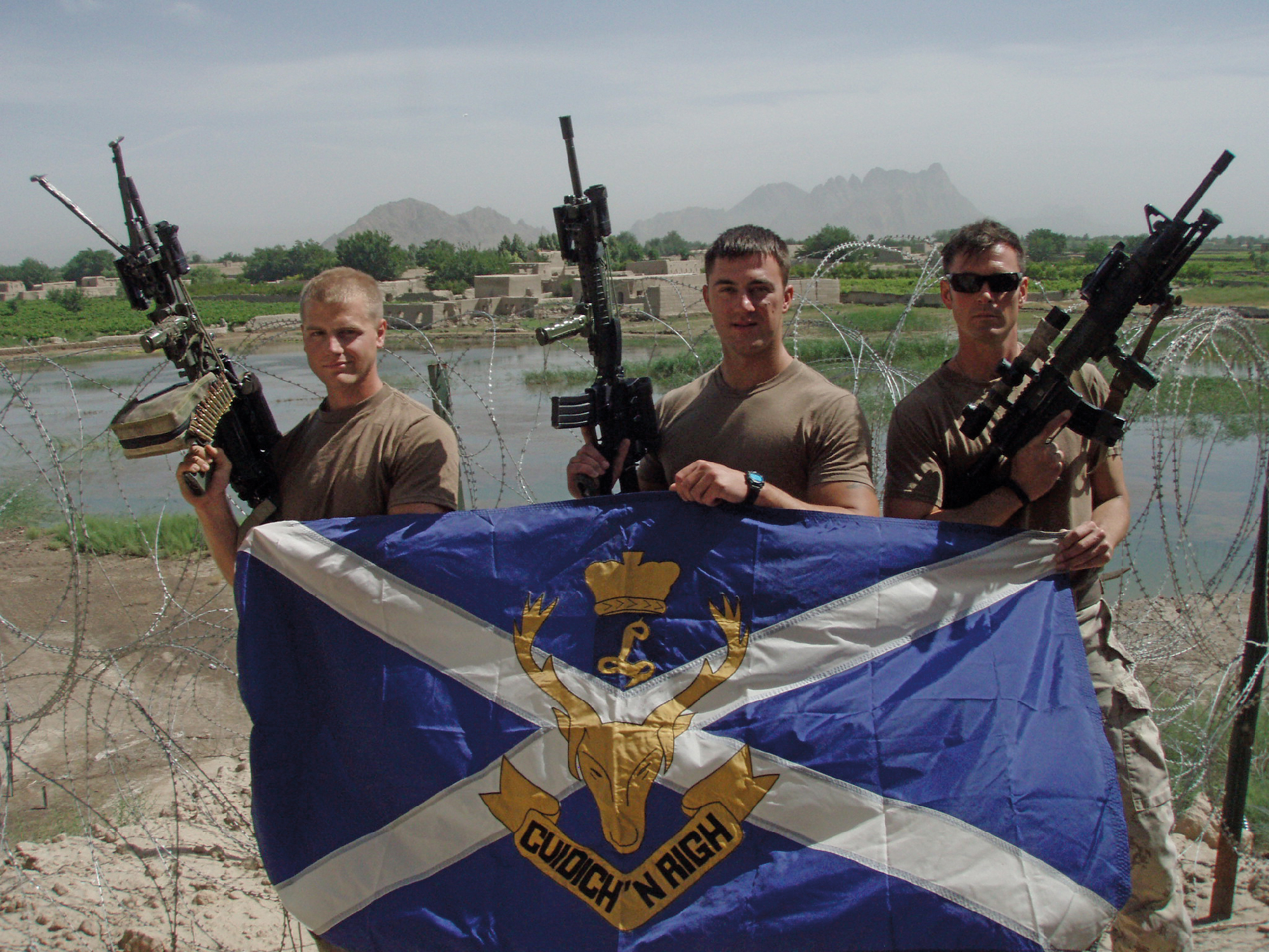 Corporals Josh Muir, Emil Kowalczyk and Max Birkner with Seaforth camp flag, on the wall at Forward Operating Base Sper wan ghar, May 2010.