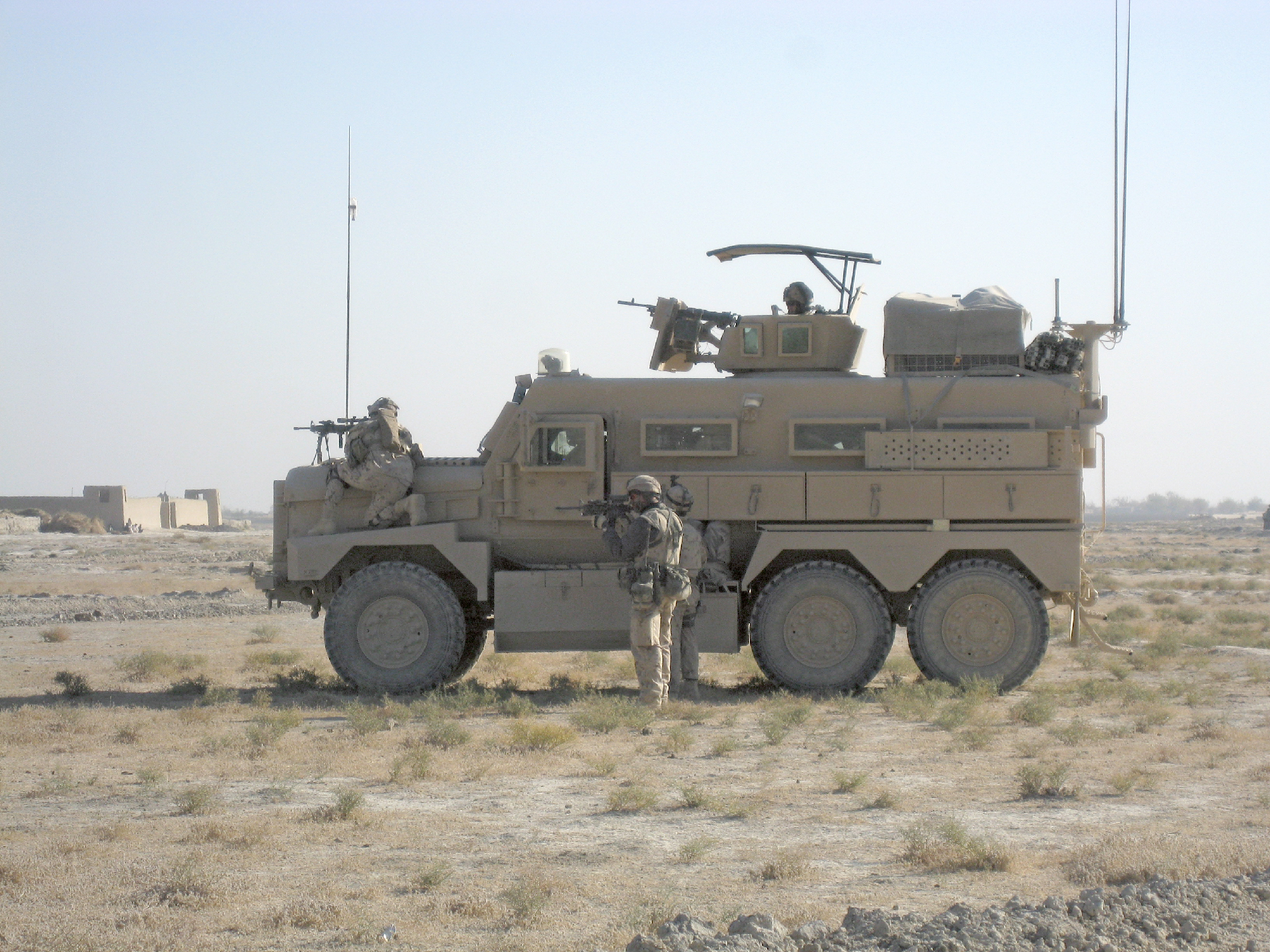 A Corporal of the Seaforth Highlanders has noticed suspect activity. He uses the fender of a Cougar to keep an eye on an individual who was paying unusual attention to the Canadian convoy outside the village of Nakhonay, Kandahar province, Nov. 2009. The vehicle was used by a Canadian Explosives Ordinance Disposal team.