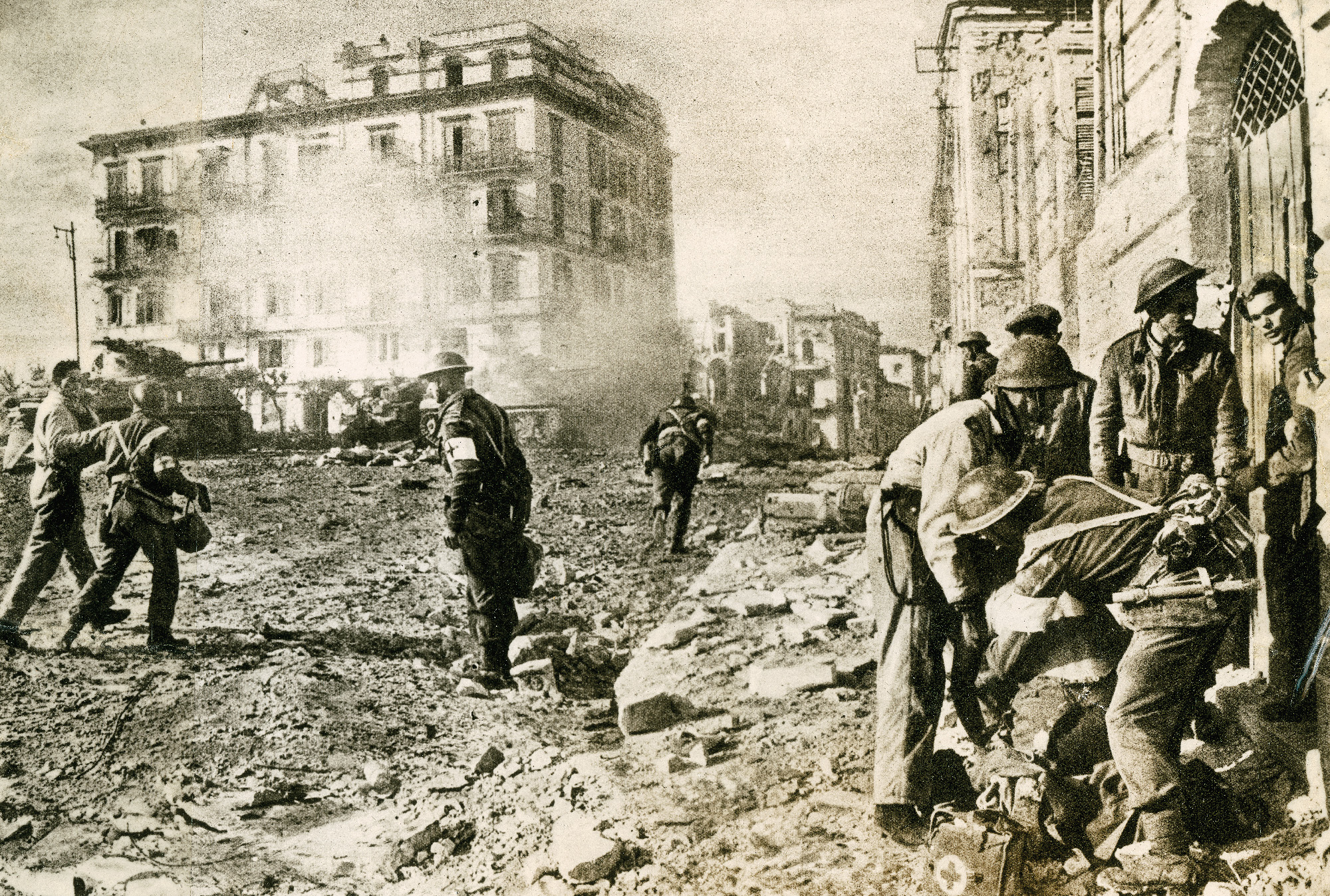 Christmas 1943: Dead Horse Square, Ortona, Italy. So named for the principal landmark – a horse that had been killed early in the battle – this was the site of a desperate battle to dislodge the enemy from a church and a school nearby. This is one of the very few combat photos in our collection. This scene was being swept with sniper fire when the photo was taken. In the foreground we see medics treating two wounded men. The wounded man on the left was a tank officer shot by a sniper while in the hatch of his tank. In the centre a medic sprints toward another casualty. The wounded man on the right is an infantryman who was also hit by a sniper, and in the background we see two Sherman Tanks firing at the enemy.