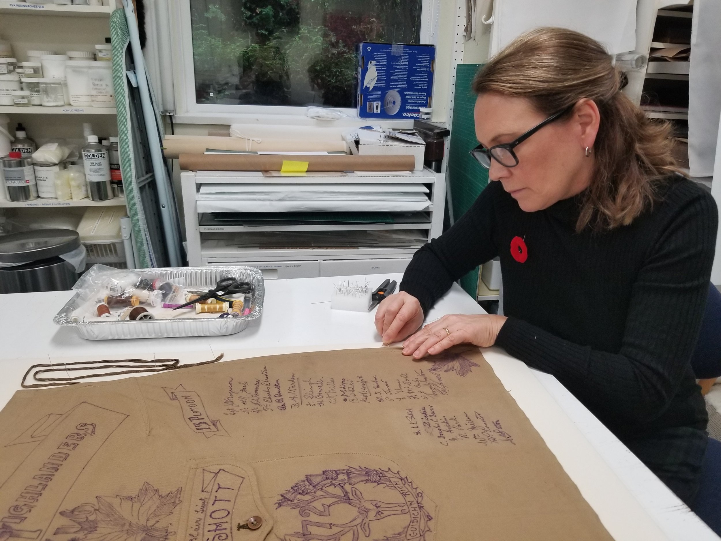 Conservator Sarah Spafford-Ricci sewing apron onto linen mount