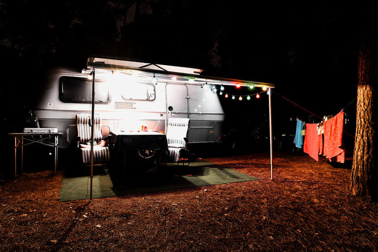 87297899 - retro vintage camping caravan trailer at night in a forest with lights, chairs and a table