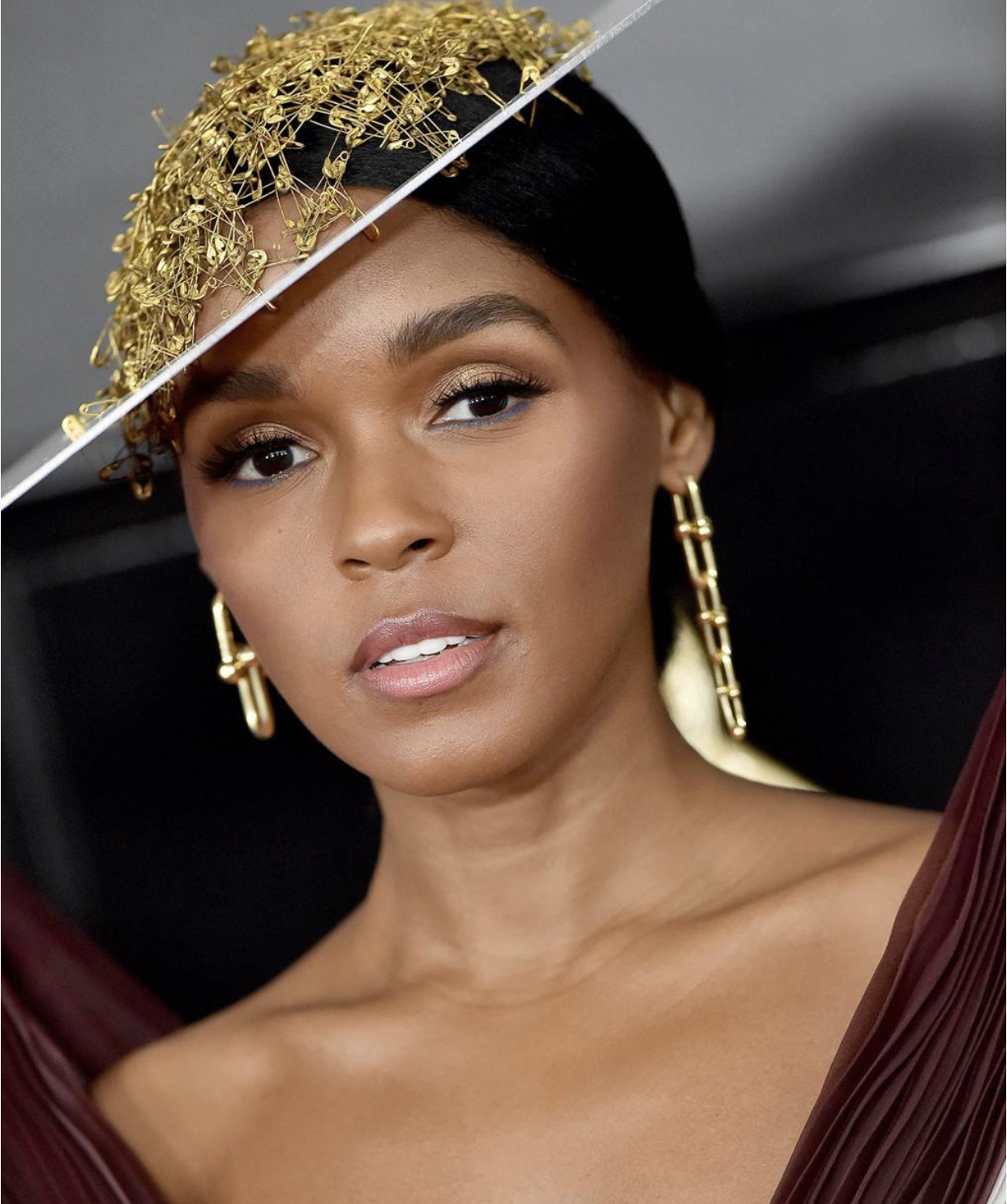 Janelle Monáe wearing Tiffany & Co. mismatched bold gold chain link earrings. -