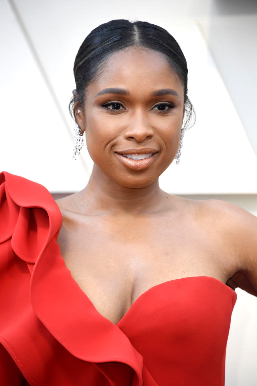 """Jennifer Hudson's Monochrome Moment - Long before she took the stage to belt out """"I'll Fight"""" (to mixed reviews, says the Internet), JHud was looking positively smashing in red on the red carpet. The slightly wispy center-parted updo was a brilliant choice, drawing focus to Hudson's flawlessly symmetrical face. The icing on the cake? Those mocha eyes, cheeks and lips. Stunning."""