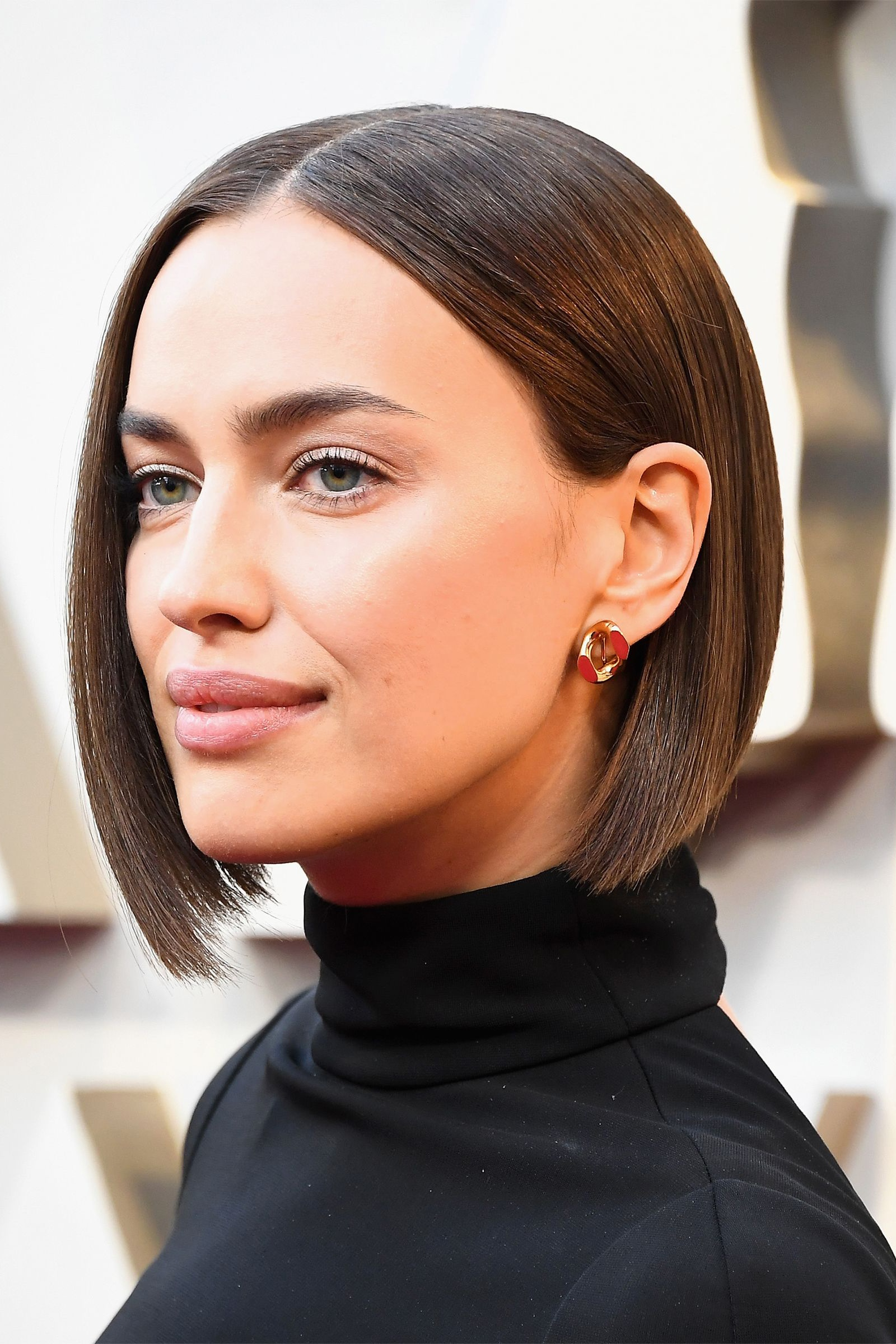 Irina Shayk's High-Shine Precision Bob - Bradley Cooper's Significant Other looked utterly amazing at the Oscars because of the handiwork of two individuals: Hair god Harry Josh and makeup whiz Tatyana Makarova for Marc Jacobs Beauty. For the big night, Josh whacked a few inches off Shayk's previous lob before coaxing her chocolate locks into a state of serious high shine. As for the maquillage, Makarova paired a smokey eye with a glossy nude lip. Dewy and dazzling, with arguably the best coif of the evening. Winning.