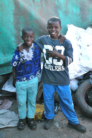 Fred and his brother mukonda in 2013 standing outside their plastic tarp home before living with Arise Africa.