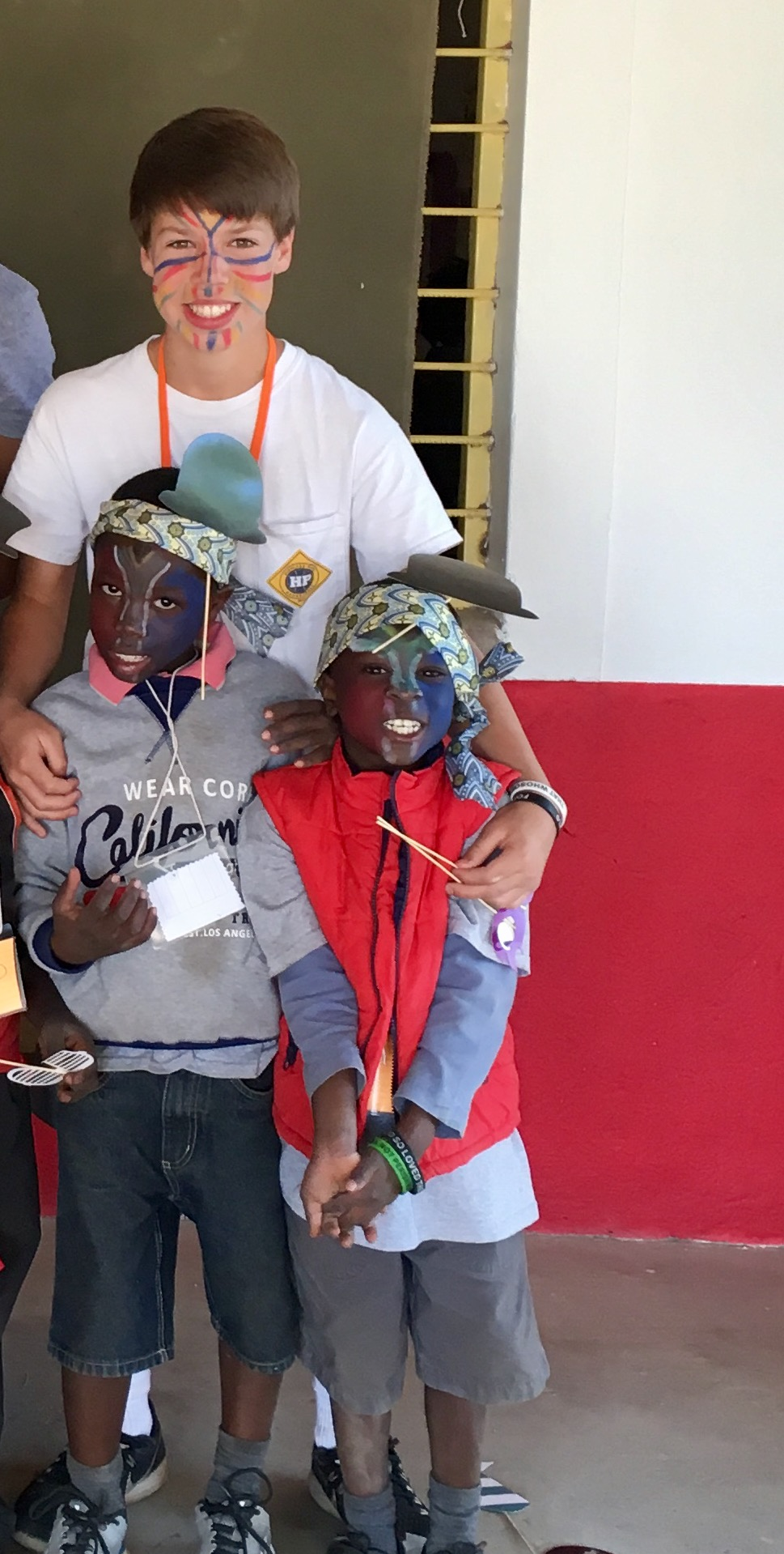 Lovemore (right) and Muyunda (left) with their Bible Camp counselor, Carson.