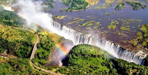 VICTORIA FALLS, OR MOSI-OA-TUNYA (TOKALEYA TONGA:  THE SMOKE THAT THUNDERS ), IS A WATERFALL IN SOUTHERN AFRICA ON THE ZAMBEZI RIVER AT THE BORDER OF ZAMBIA AND ZIMBABWE.