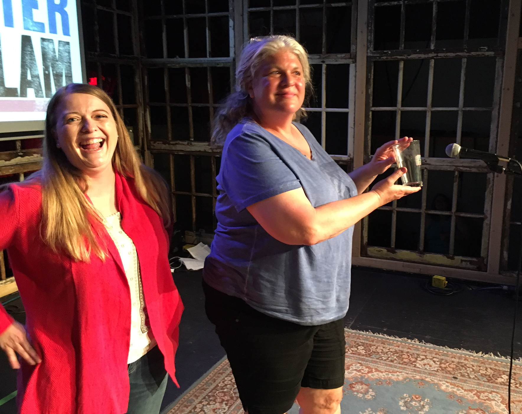 Emcee Donna Talarico looks on as Linda Silberman shows off her prized pint glass.