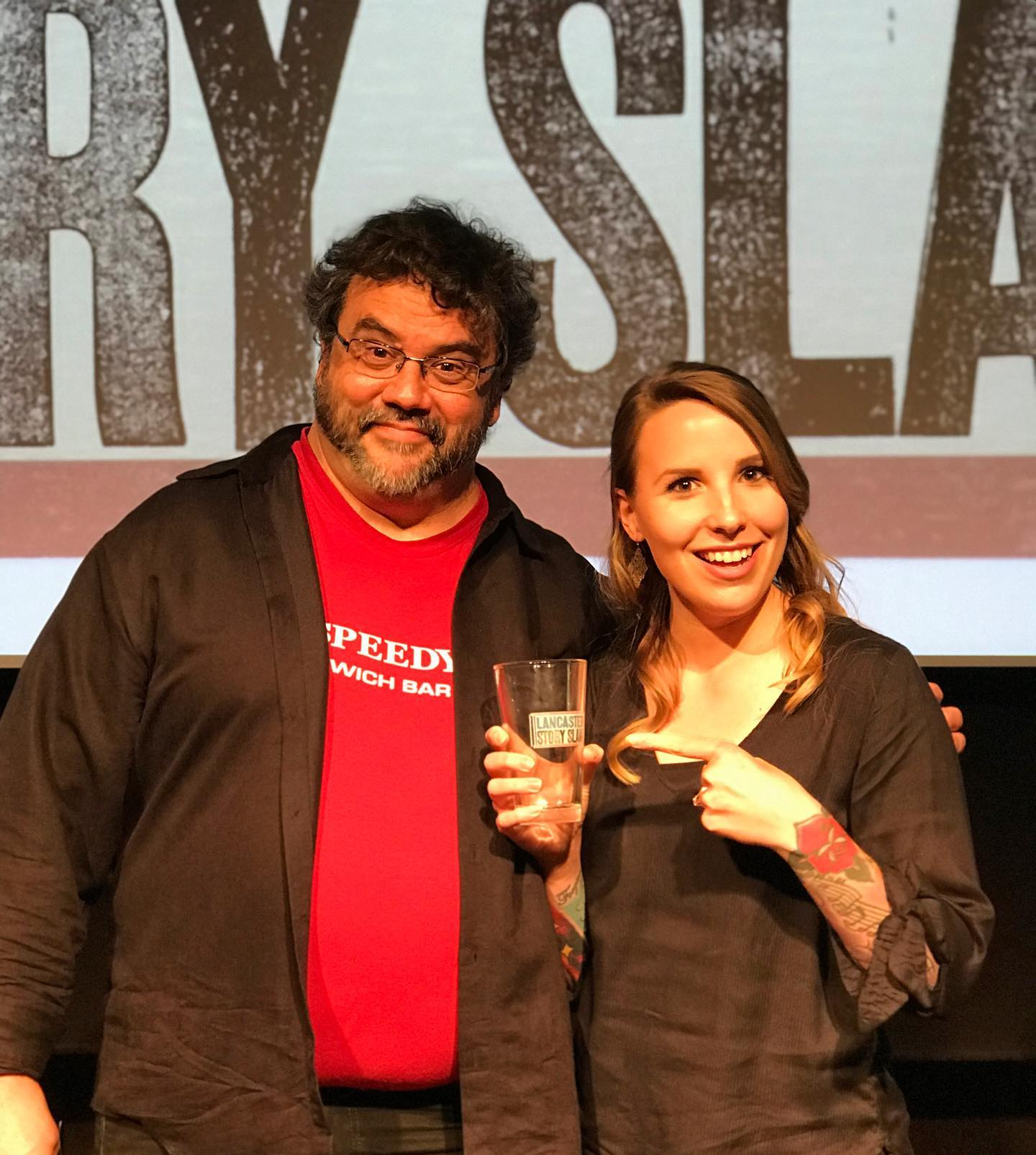 Pictured are David Smith (emcee) with our winning storyteller, Gina Melasecca, who won our prized pint glass and a spot in the Grand Slam in November!