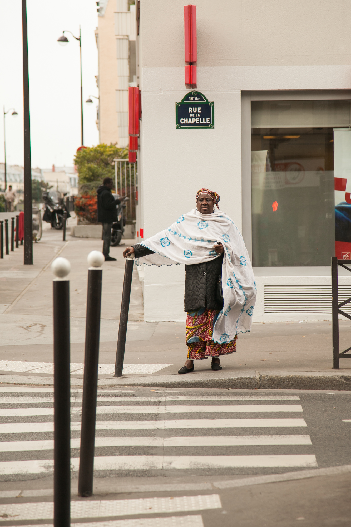 African woman in traditional dress waits to cross Rue Marx Dormoy.