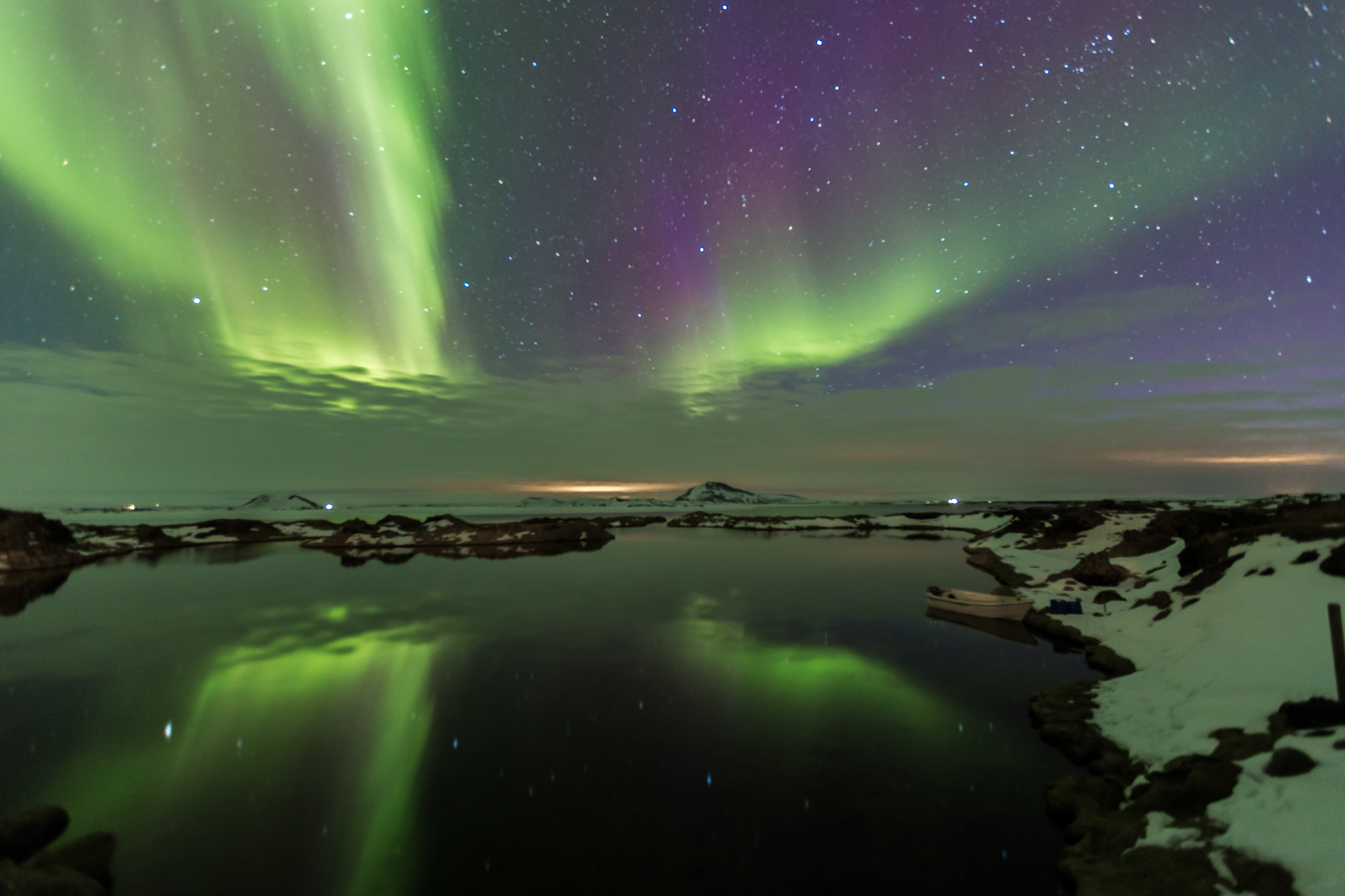 The northern lights shining over the peaceful pond in Myvatn