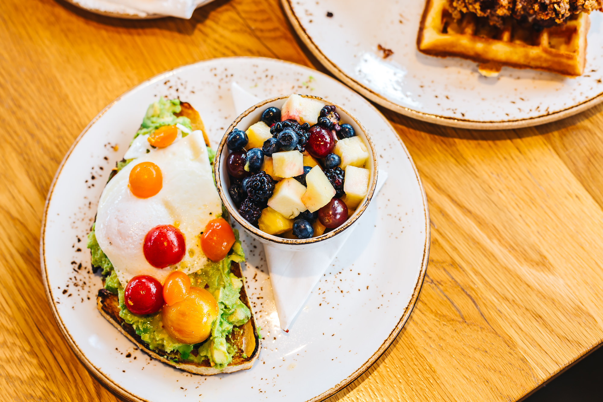 AVOCADO TOAST WITH FRIED EGG AND A BOWL OF FRUIT - BLACKBERRIES FROM RIO'S FARM