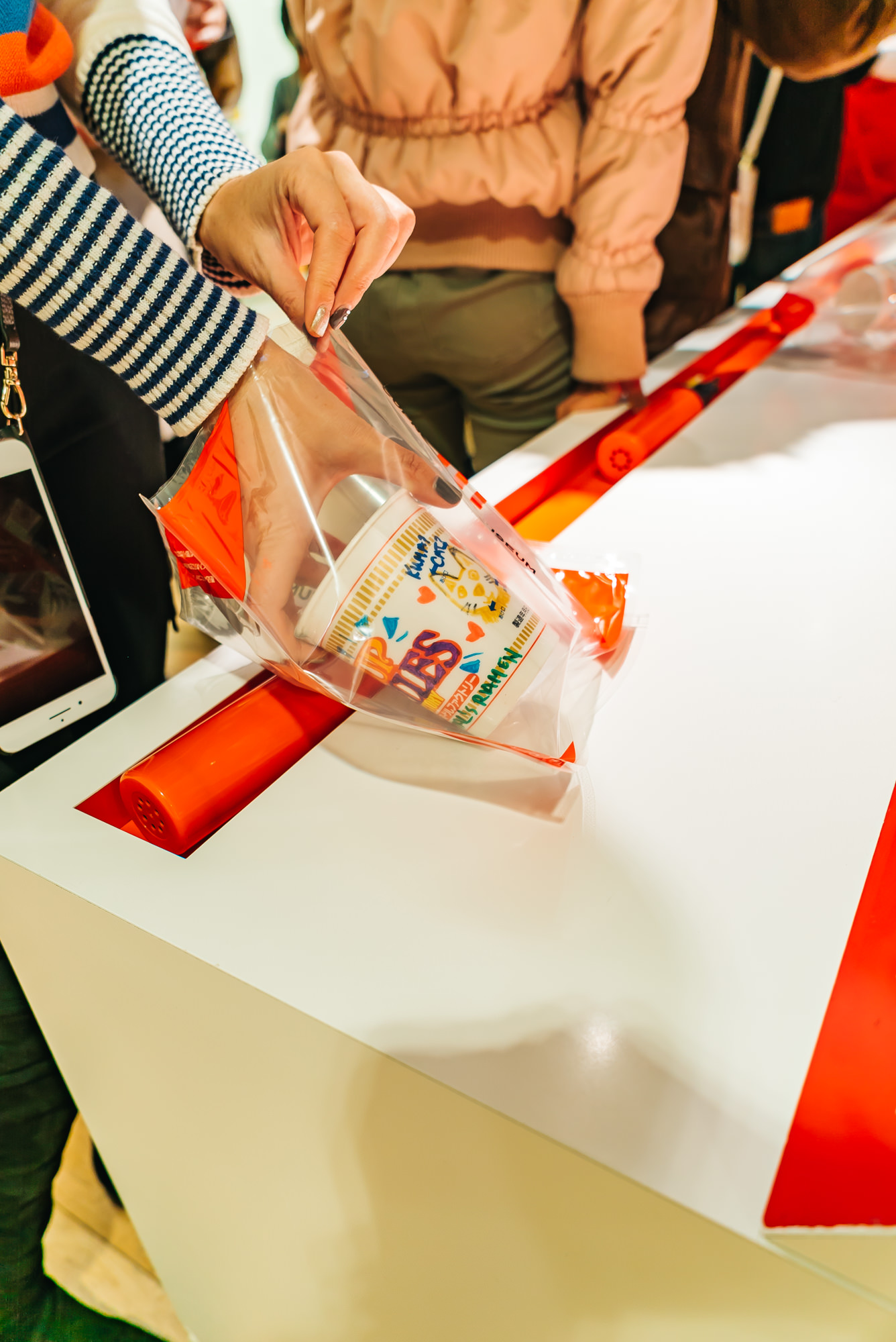 Placing our Cup Noodles in the To-Go bag