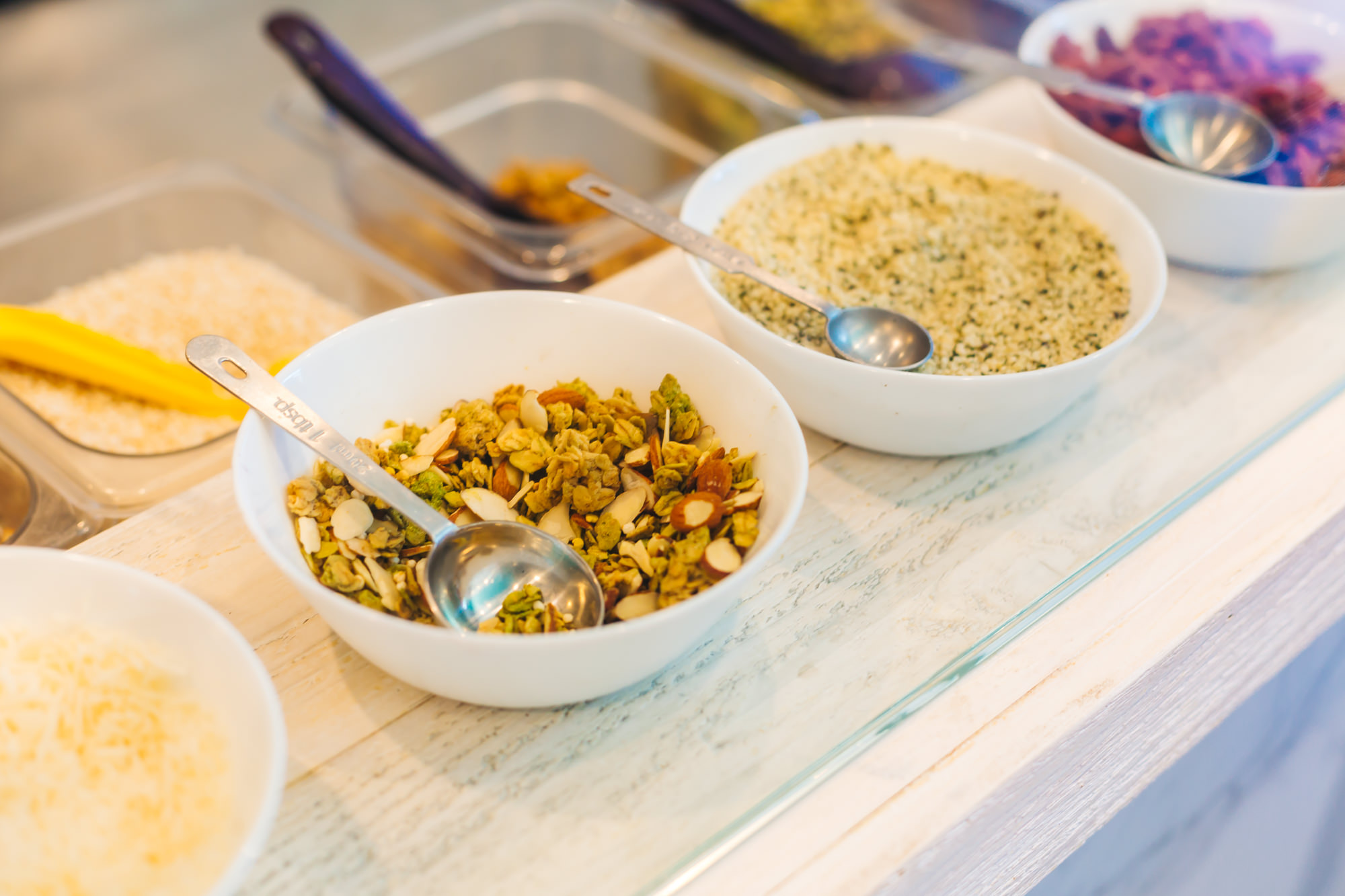 Healthy toppings for your Super Bowl like matcha granola, crunchy quinoa and coconut flakes