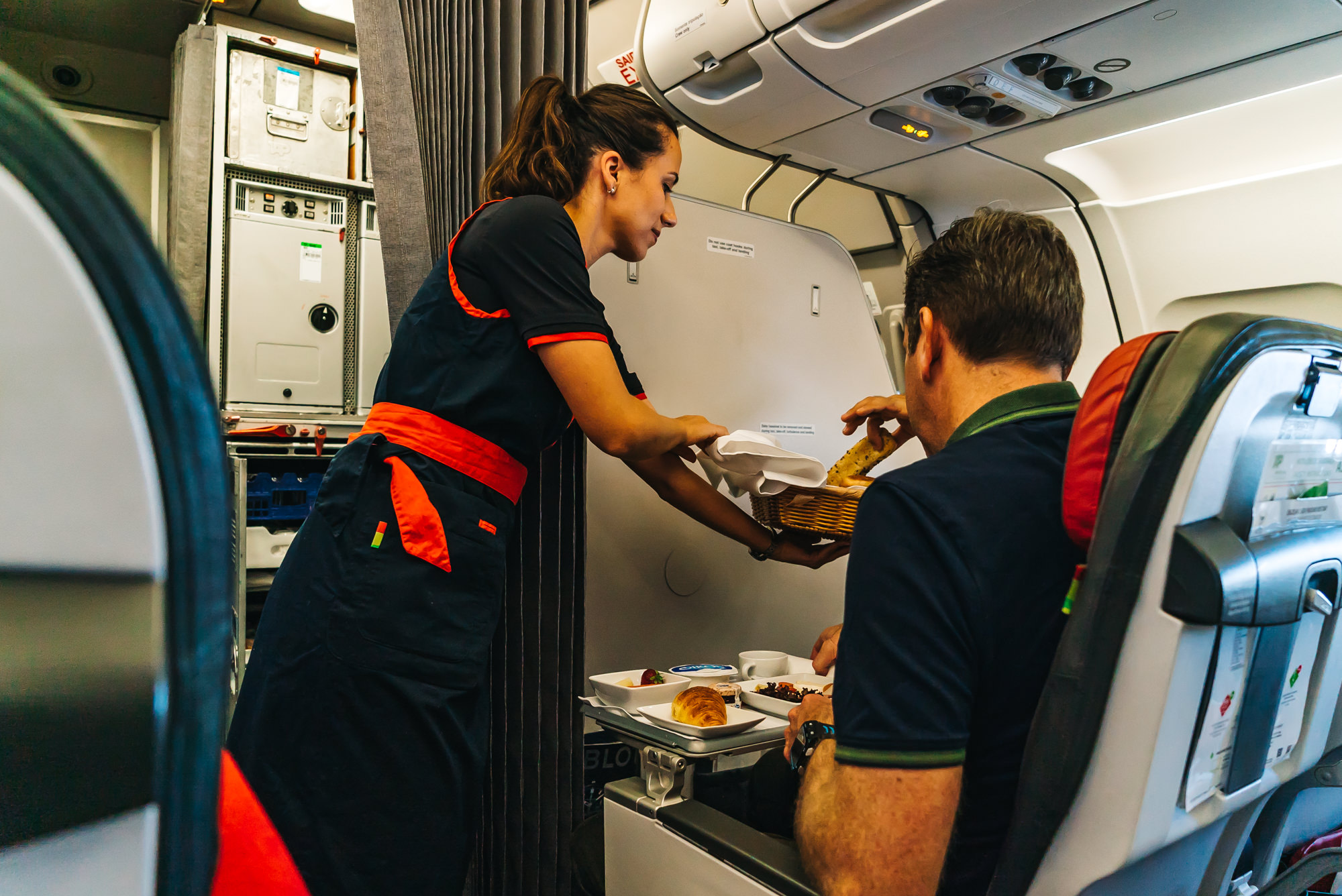 Flight attendant serving a basket of warm bread for our breakfast